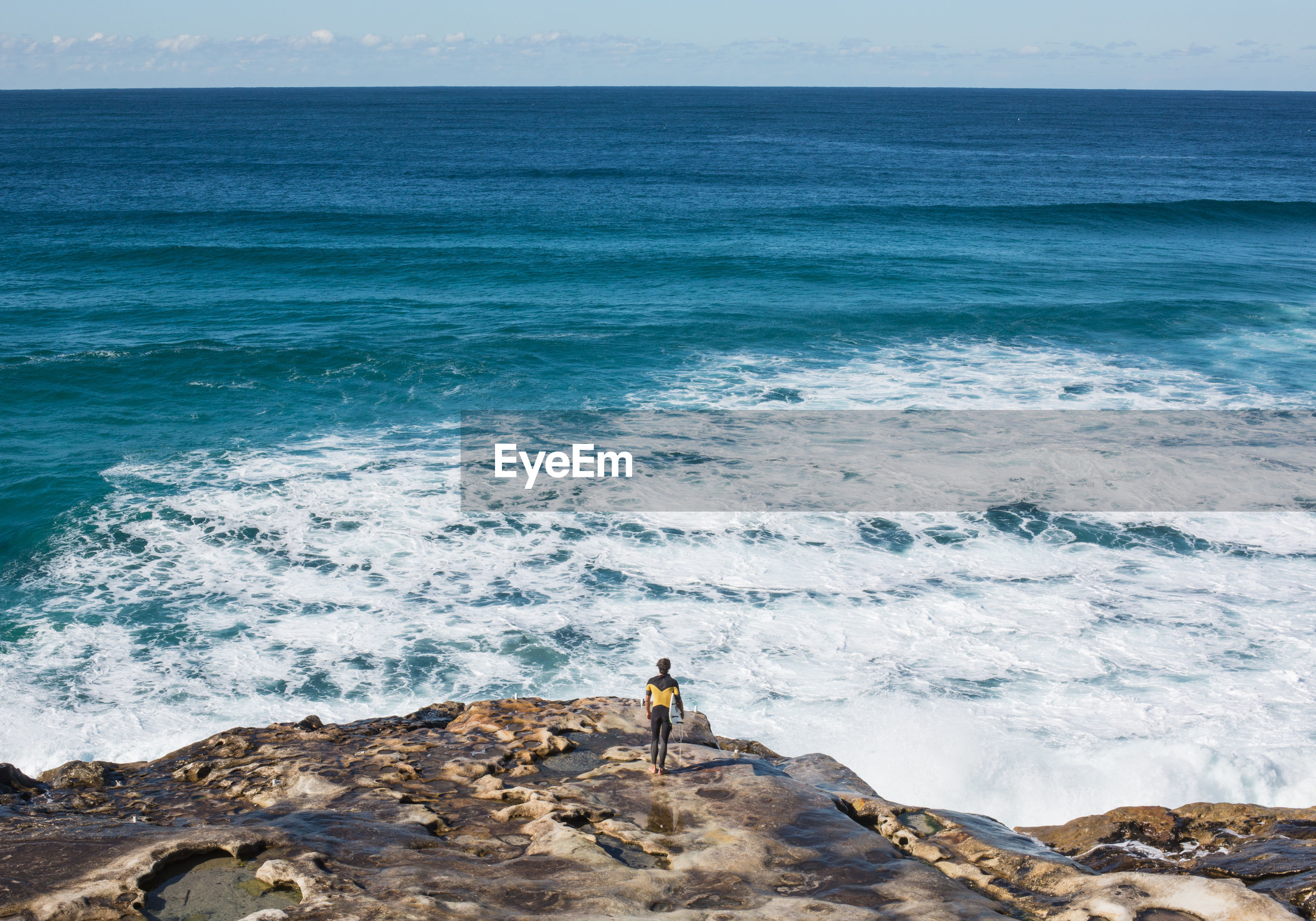 Rear view of male surfer standing on rock overlooking sea