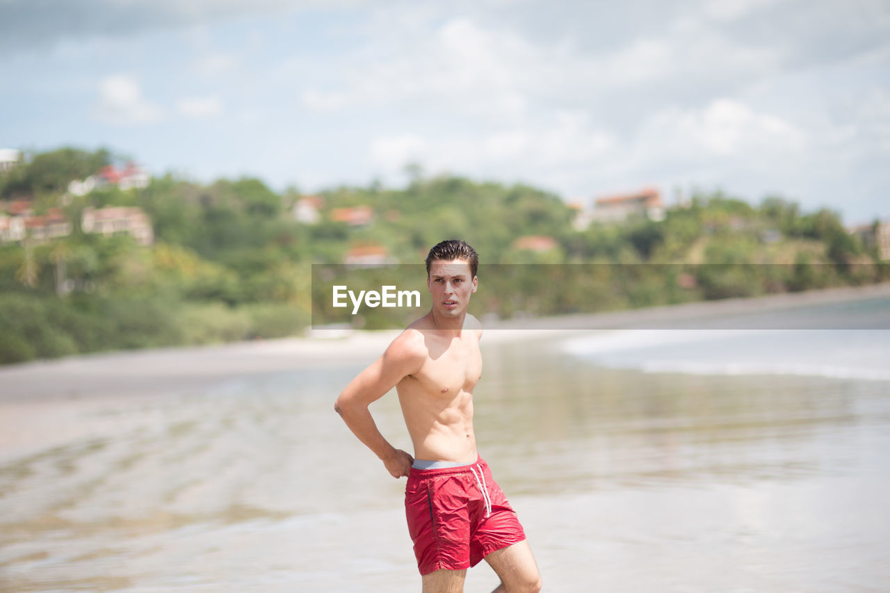 Shirtless Young Man Looking Away While Standing At Shore