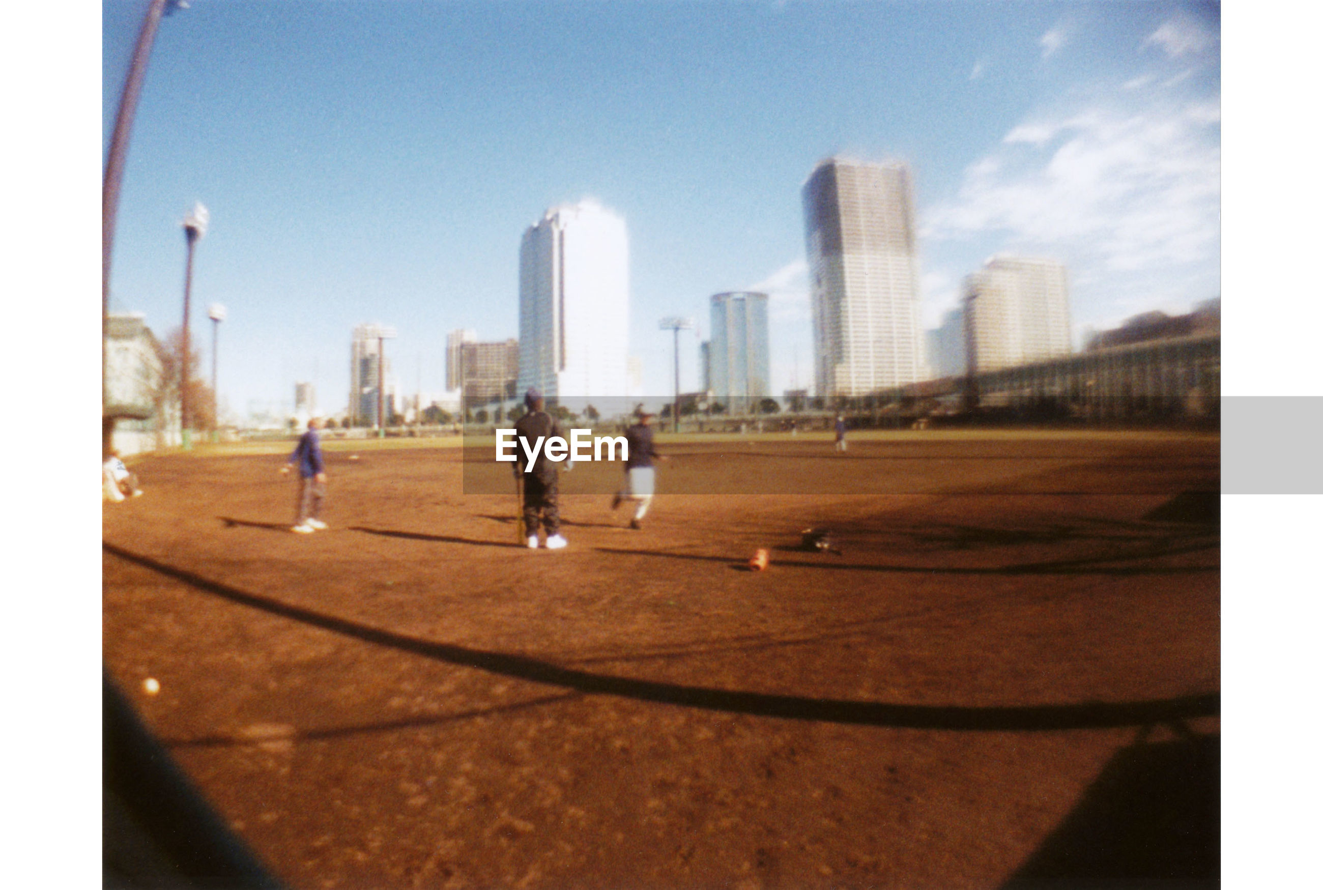 People playing on sports field against skyscrapers