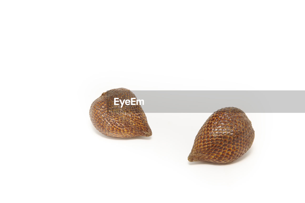 Close-Up Of Snake Fruits Against White Background