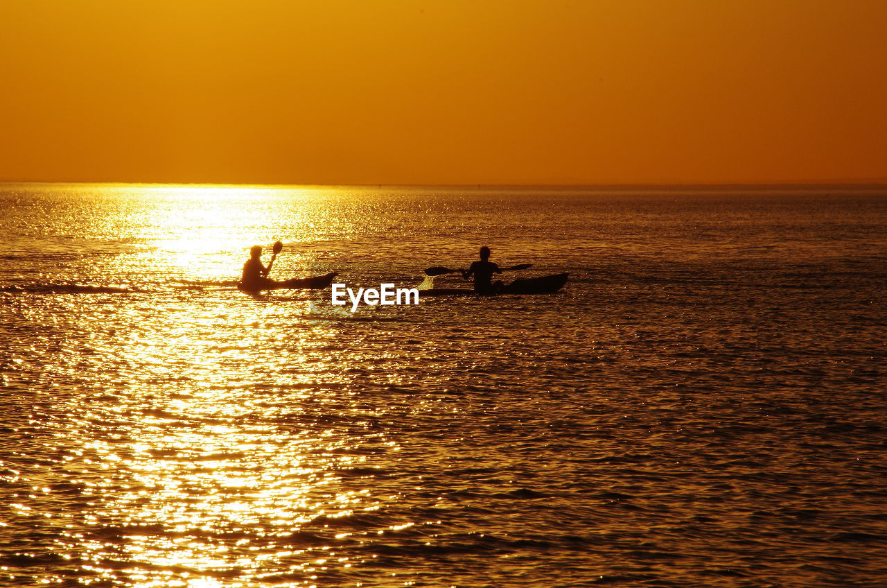 sunset, water, sea, silhouette, horizon over water, beauty in nature, orange color, scenics, nature, waterfront, real people, nautical vessel, transportation, leisure activity, sunlight, outdoors, sky, lifestyles, togetherness, men, rowing, paddleboarding, day, people