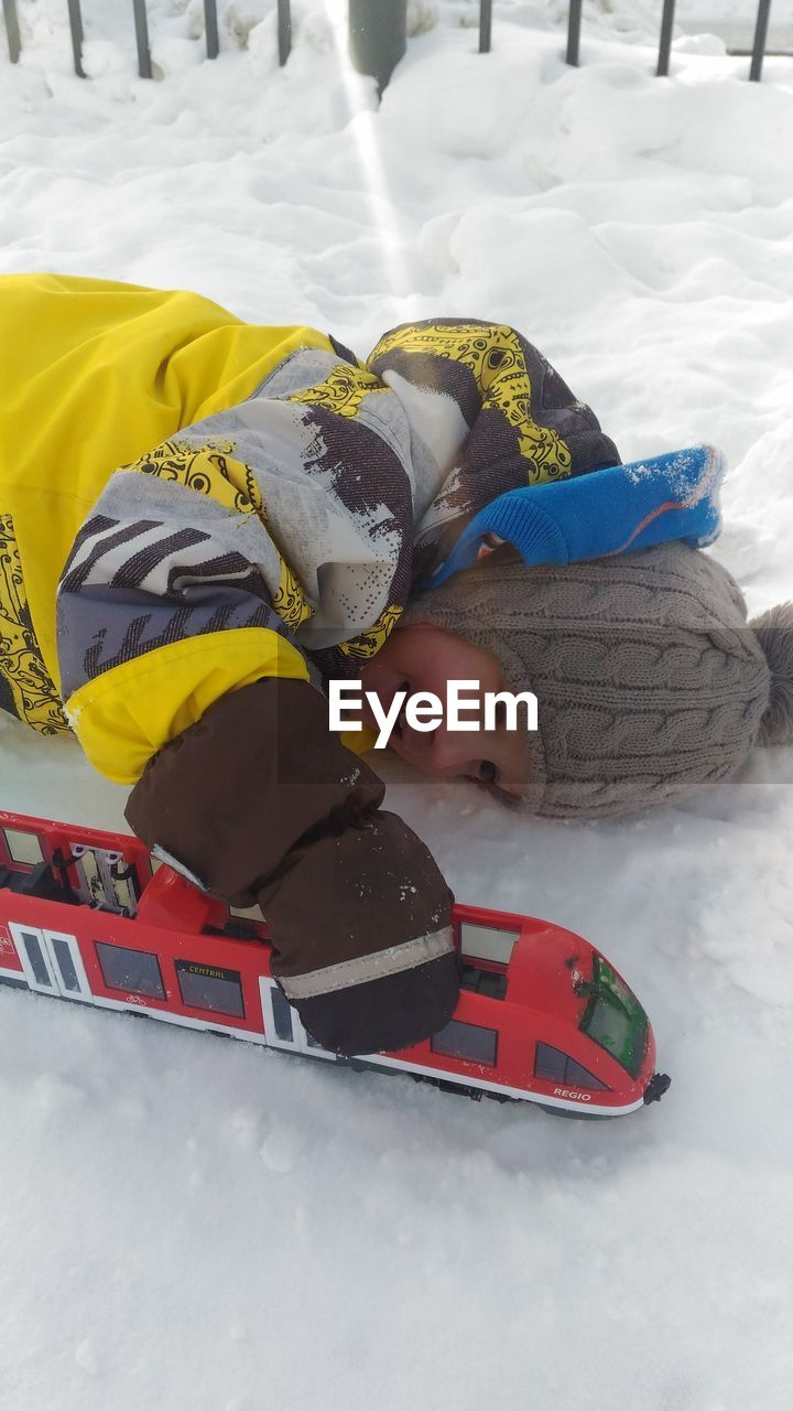 childhood, real people, winter, snow, lying down, leisure activity, one person, elementary age, boys, cold temperature, lifestyles, cute, day, playing, happiness, warm clothing, outdoors, looking at camera, full length, portrait, smiling, tobogganing