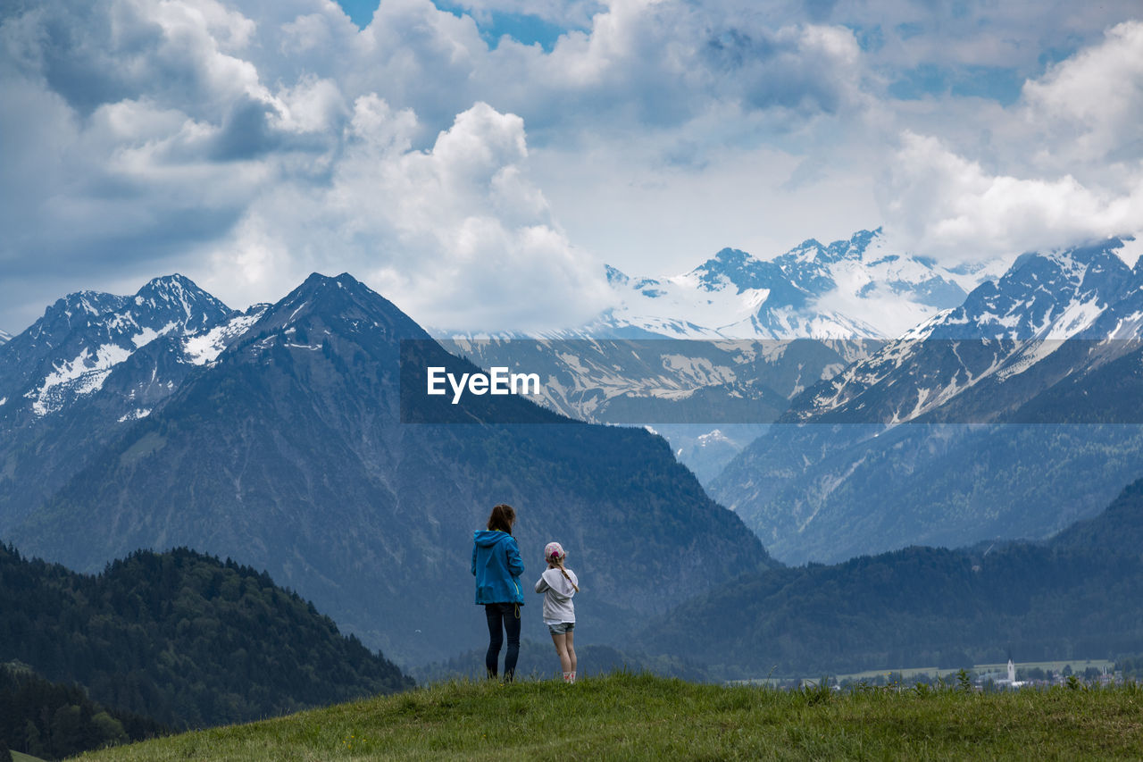 REAR VIEW OF TWO PEOPLE STANDING ON MOUNTAIN RANGE