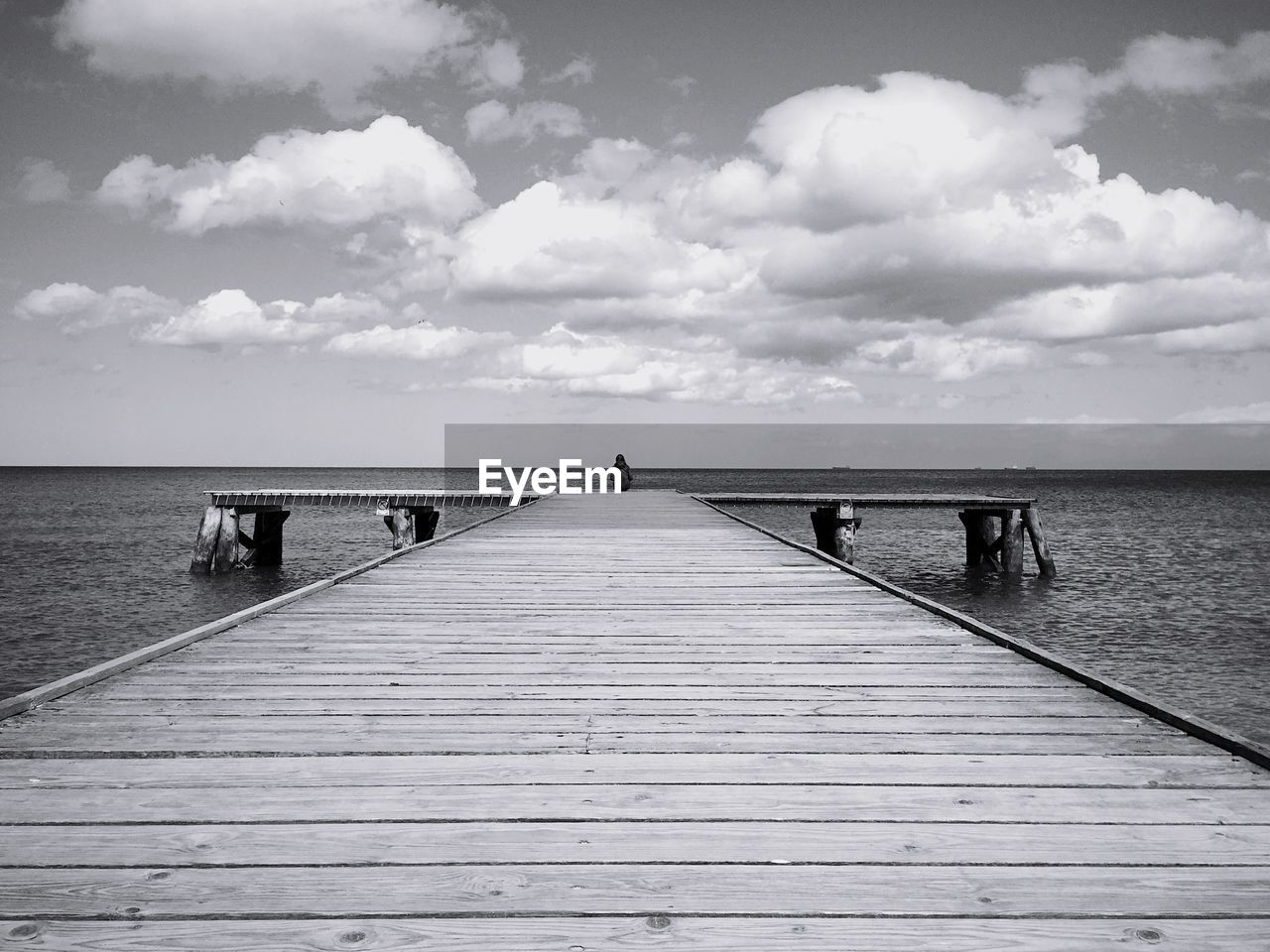 Person sitting on pier over sea against sky