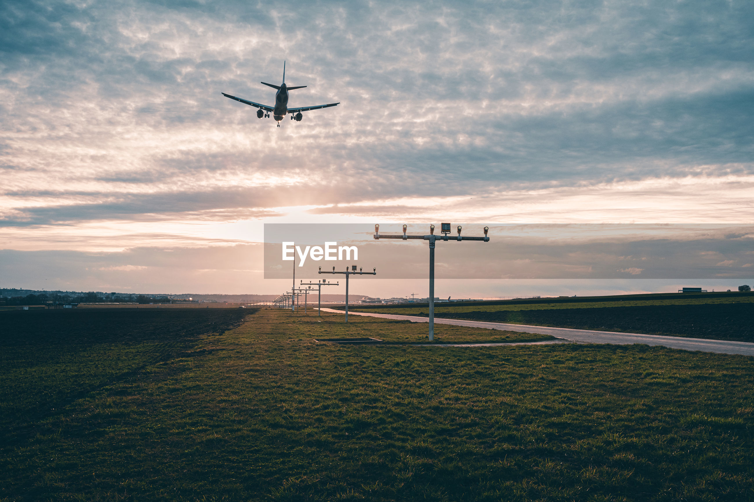 Airplane flying over land against sky during sunset