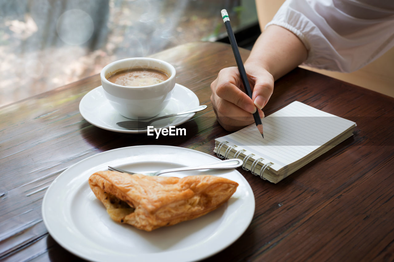 Cropped image of writing with breakfast on table