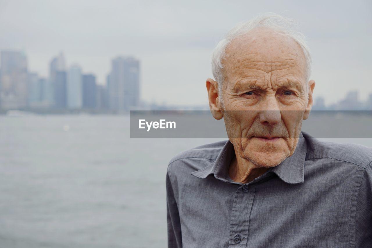 Portrait of senior man in city against sea