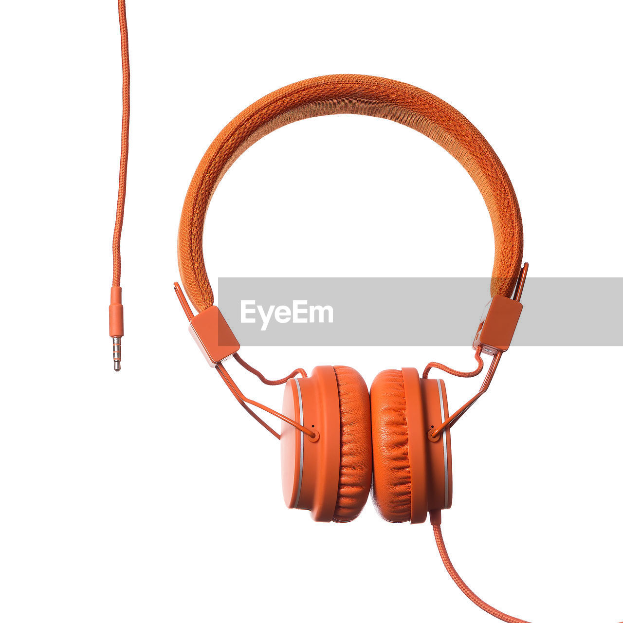Close-up of orange headphones over white background