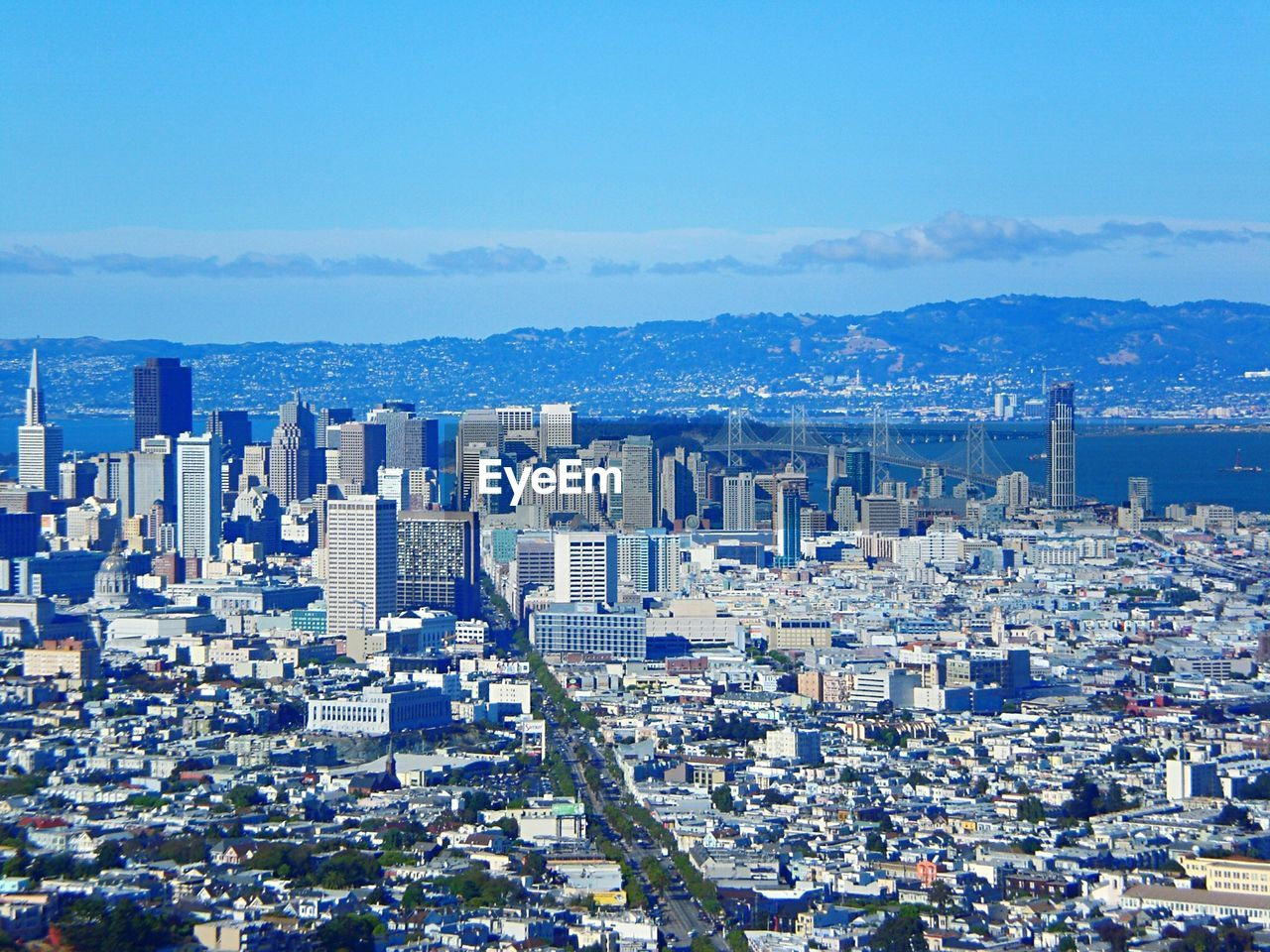 Aerial View Of Cityscape And Mountains Against Blue Sky