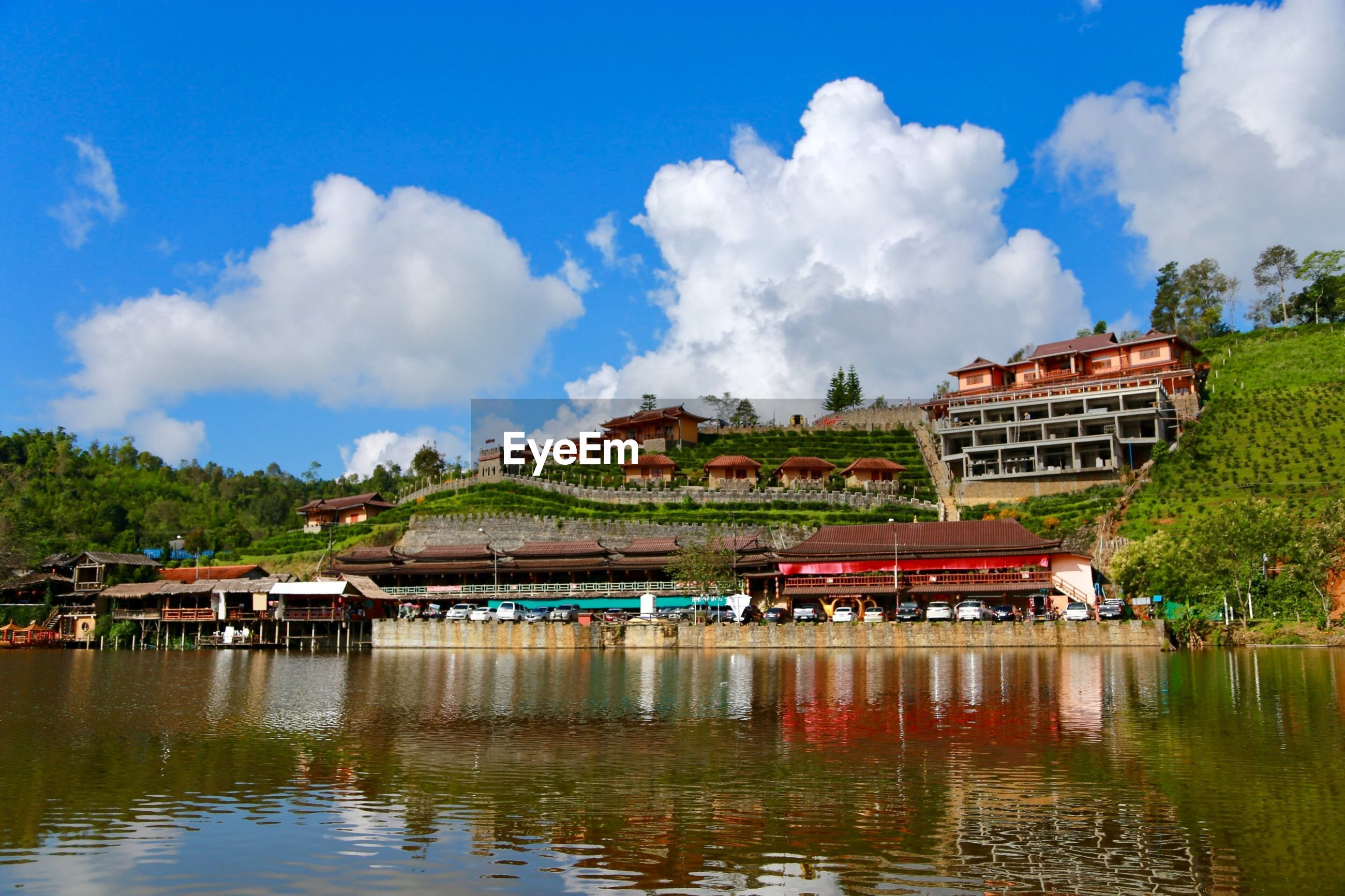 Panoramic view of buildings by river against cloudy sky