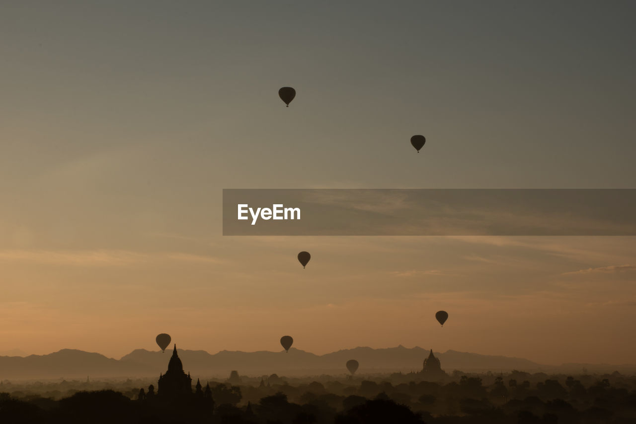 Low angle view of hot air balloons against sky during sunset