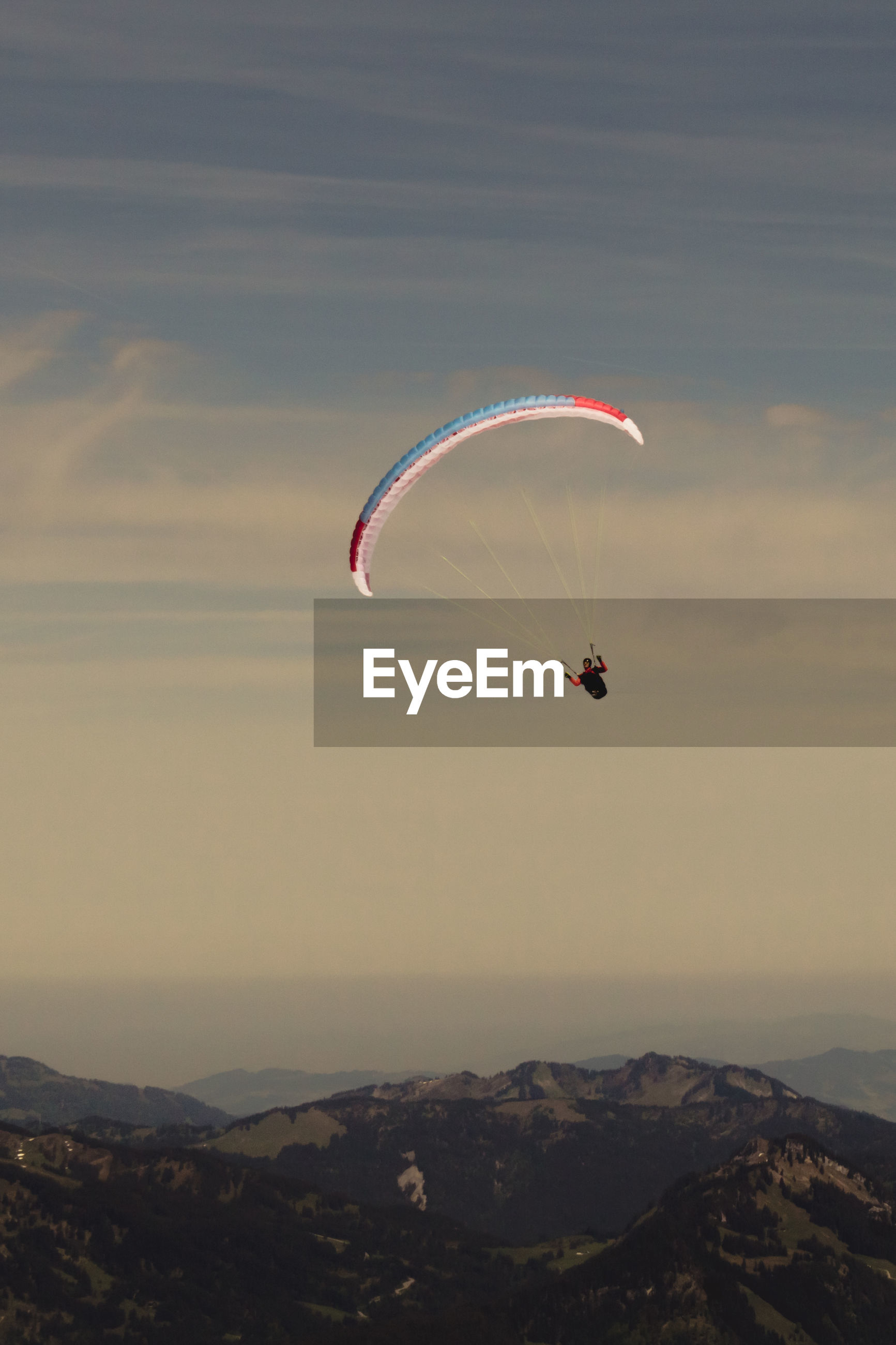 Low angle view of man parachuting above mountains at dusk
