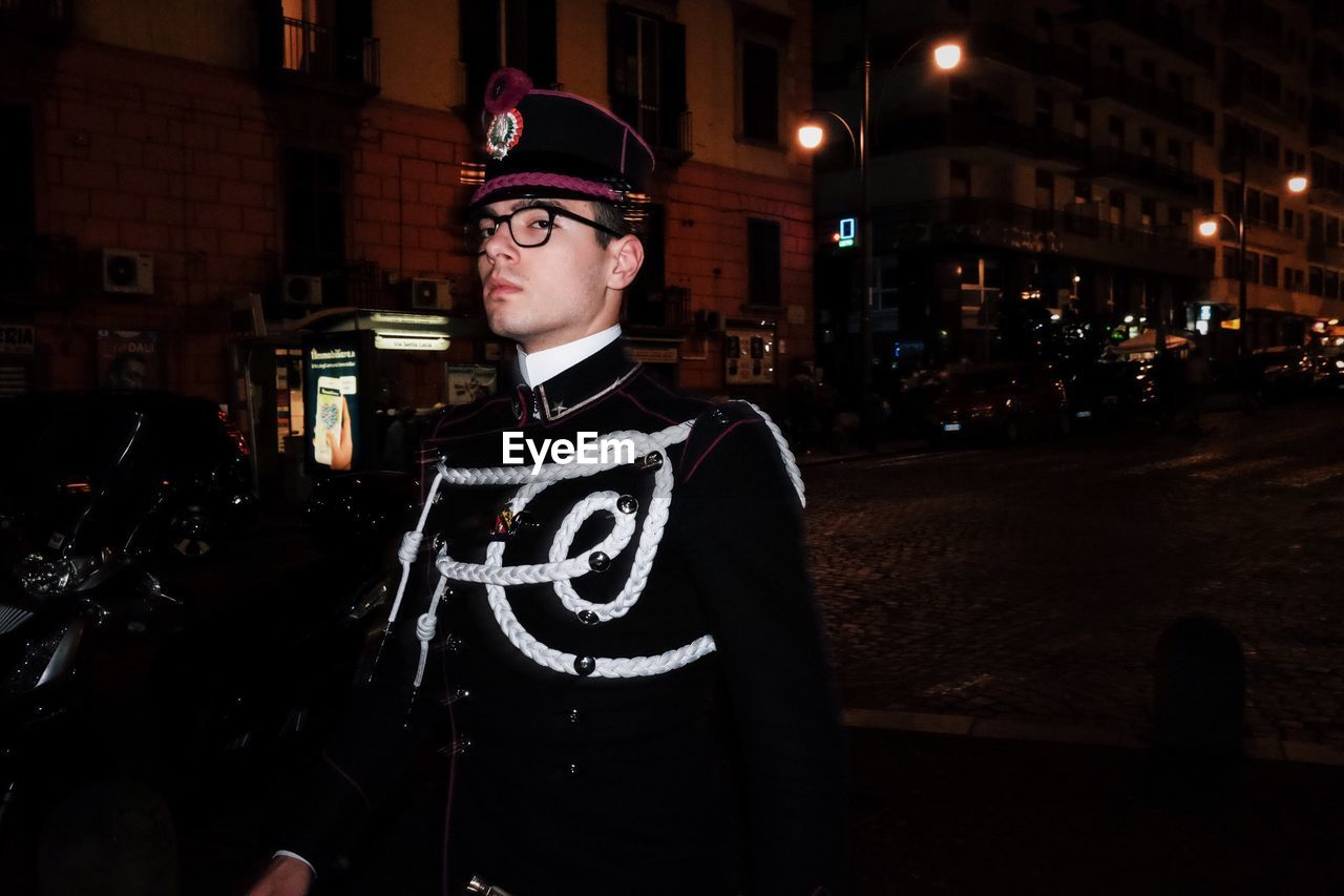 one person, architecture, building exterior, city, standing, built structure, night, young adult, waist up, illuminated, street, clothing, young men, real people, glasses, men, front view