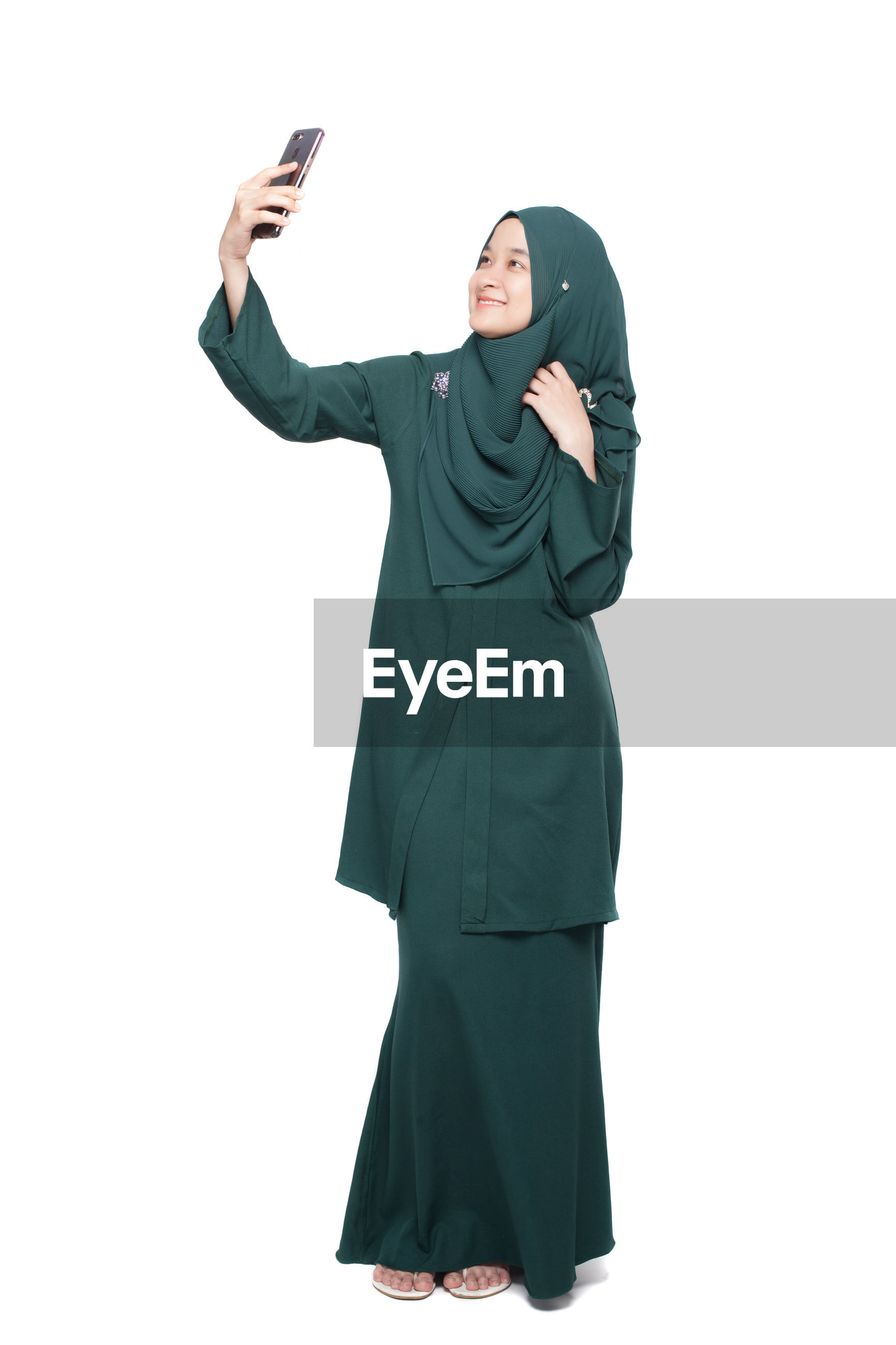 Smiling woman taking selfie while standing against white background