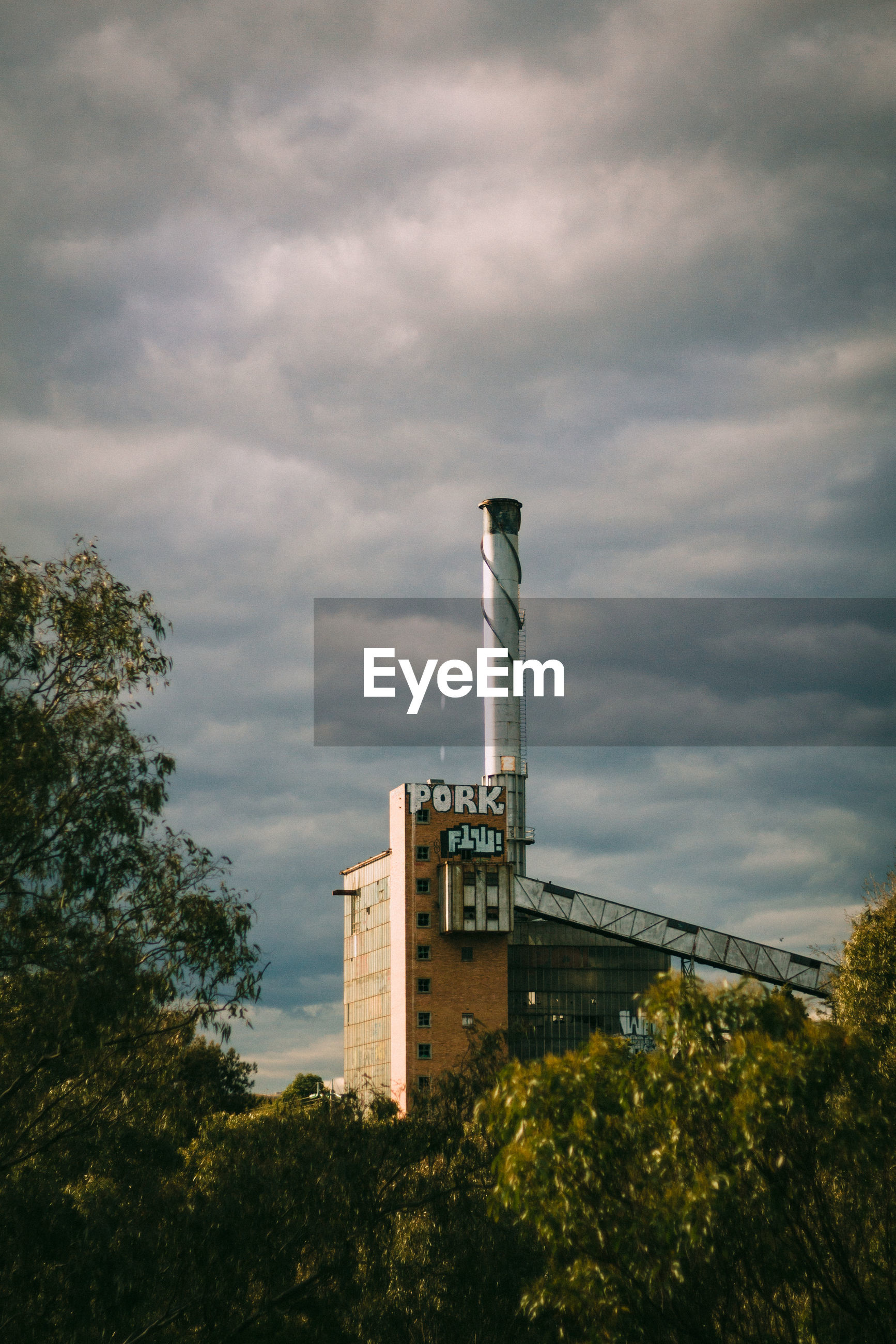LOW ANGLE VIEW OF FACTORY AGAINST CLOUDY SKY