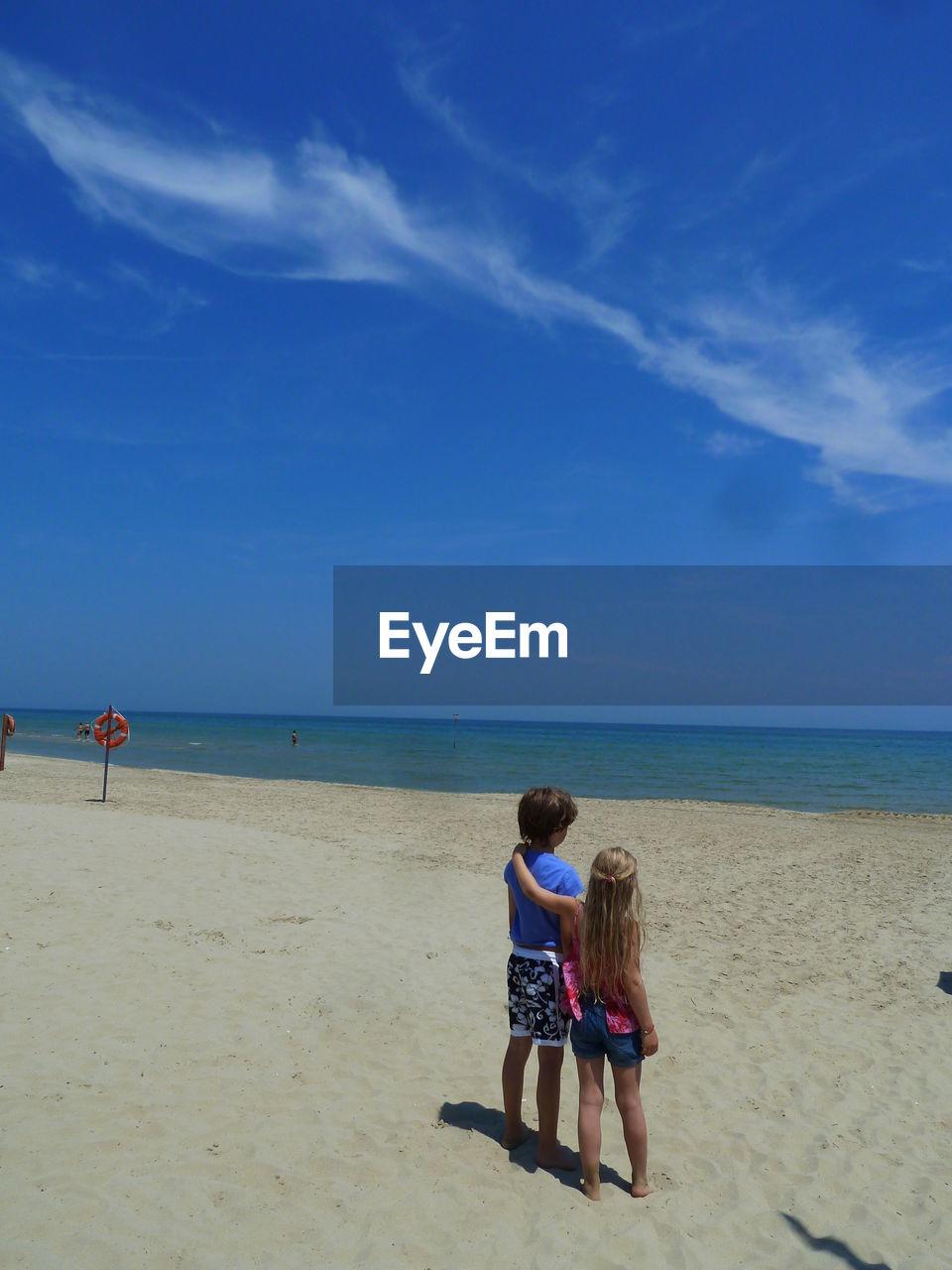 Rear view of siblings standing on sandy beach