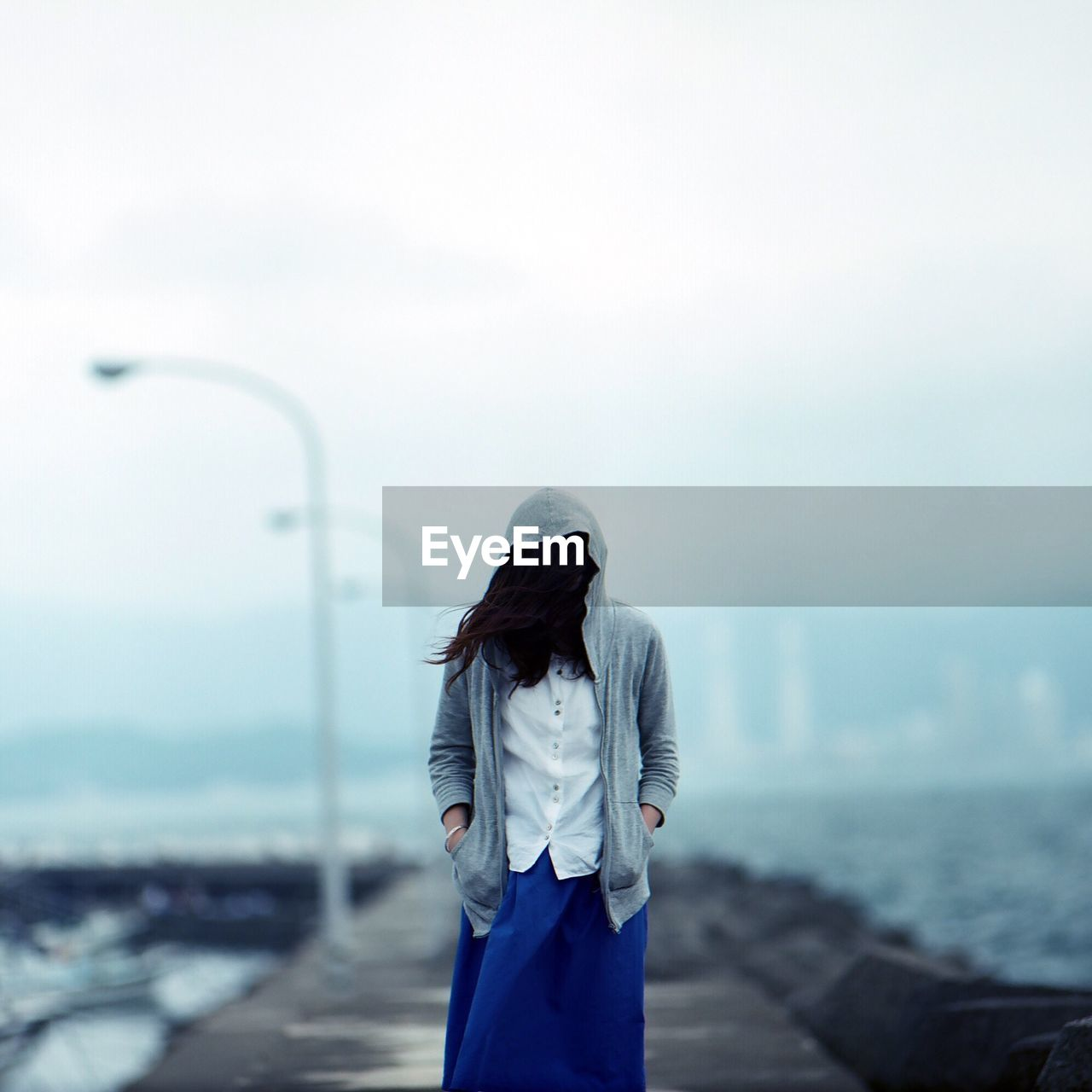 Woman Face Covered With Hair Standing On Walkway