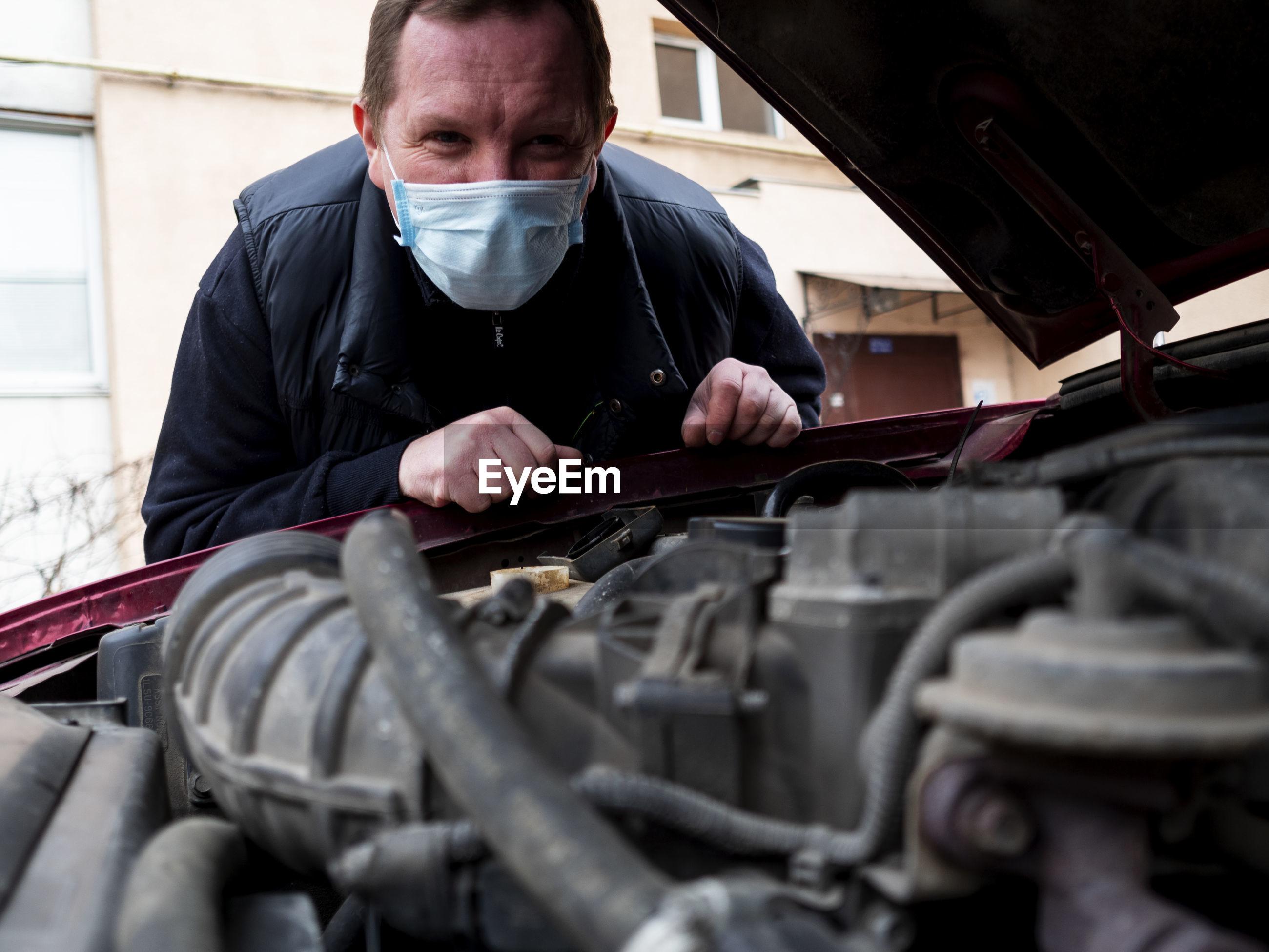 Portrait of man wearing mask examining car engine