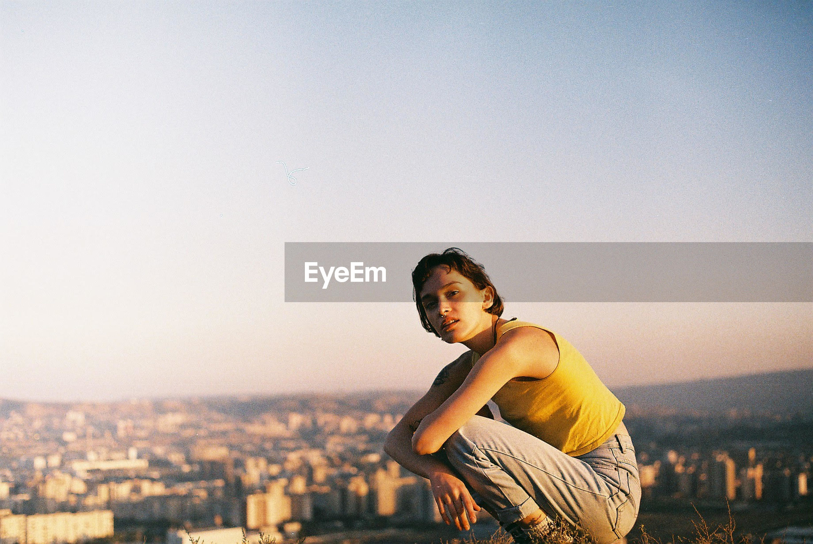 Side view portrait of woman crouching against cityscape