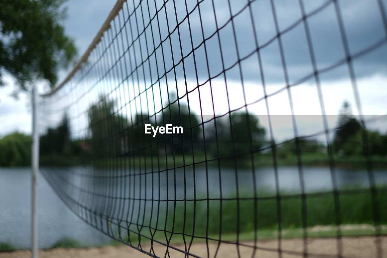 Volleyball net against lake