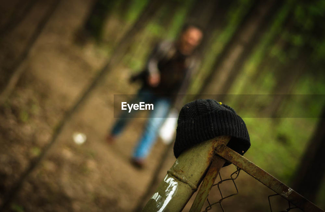 focus on foreground, one person, land, forest, day, men, nature, selective focus, adult, outdoors, tree, real people, wood - material, clothing, leisure activity, casual clothing, lifestyles, women, plant
