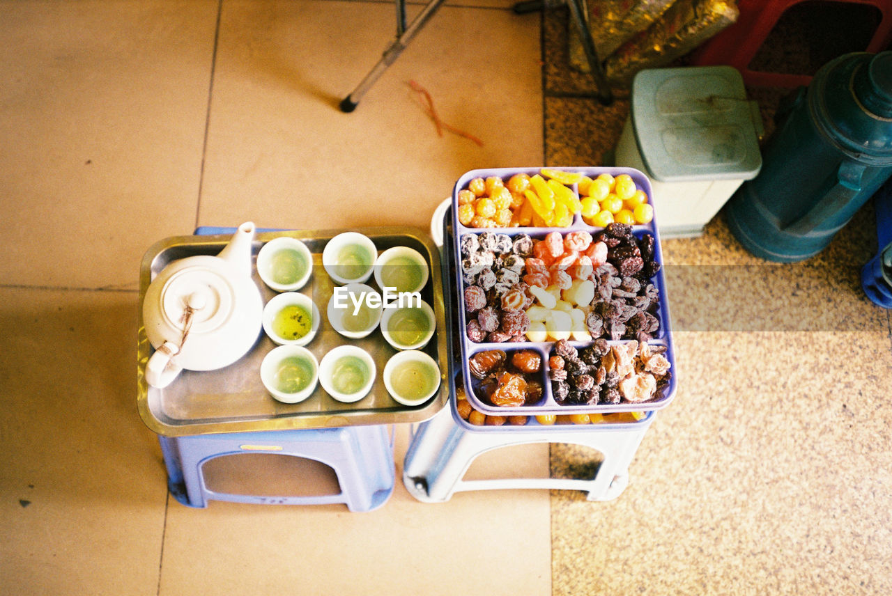 High Angle View Of Green Tea And Dried Fruits On Stool