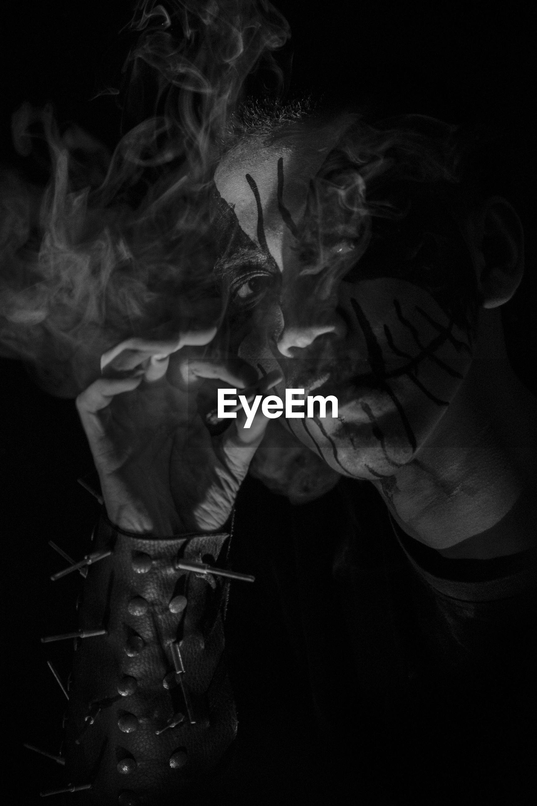 Portrait of man with face paint smoking against black background