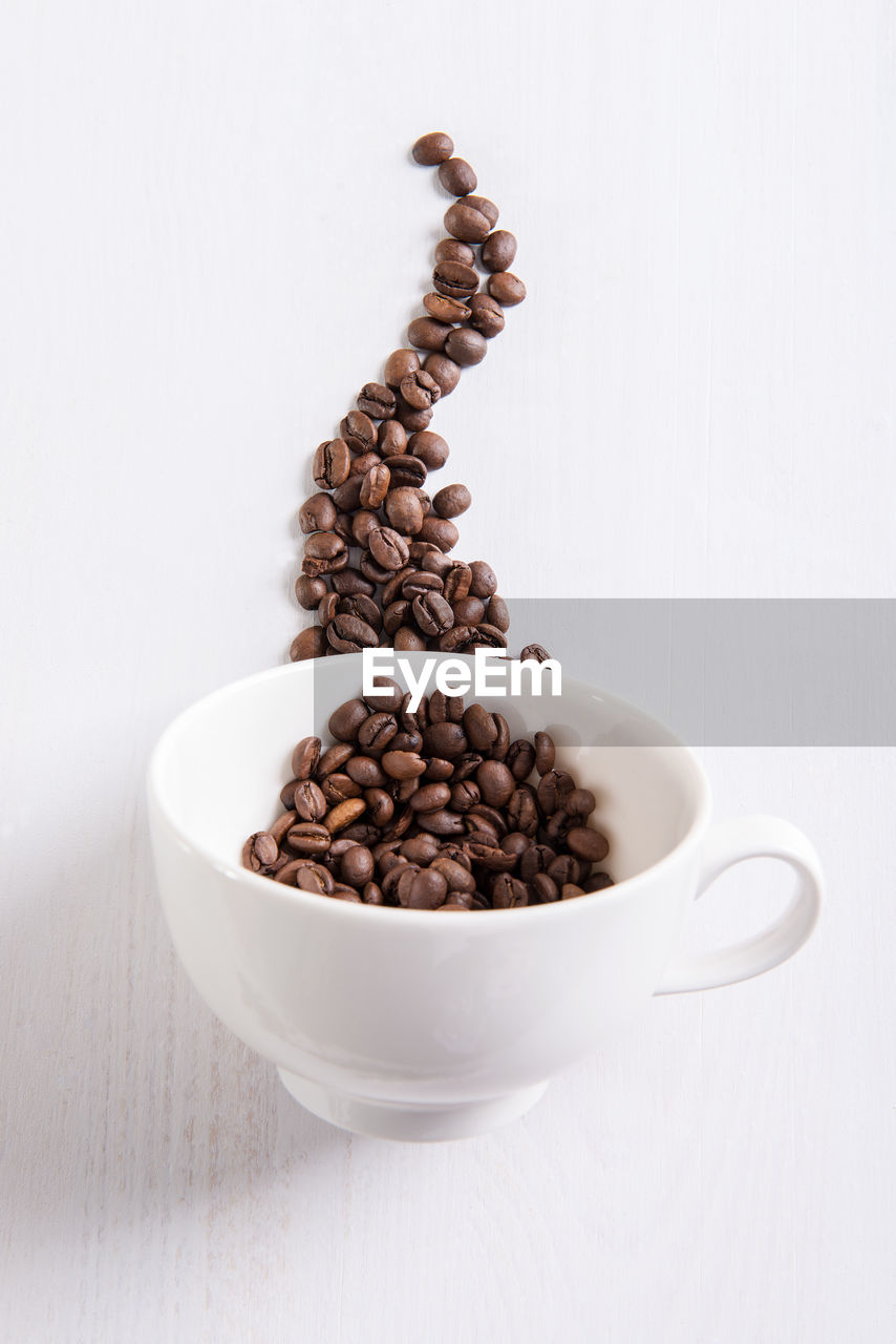 food and drink, coffee, roasted coffee bean, coffee - drink, still life, cup, white background, indoors, food, studio shot, mug, brown, coffee cup, no people, freshness, large group of objects, white color, table, copy space, close-up, caffeine, crockery