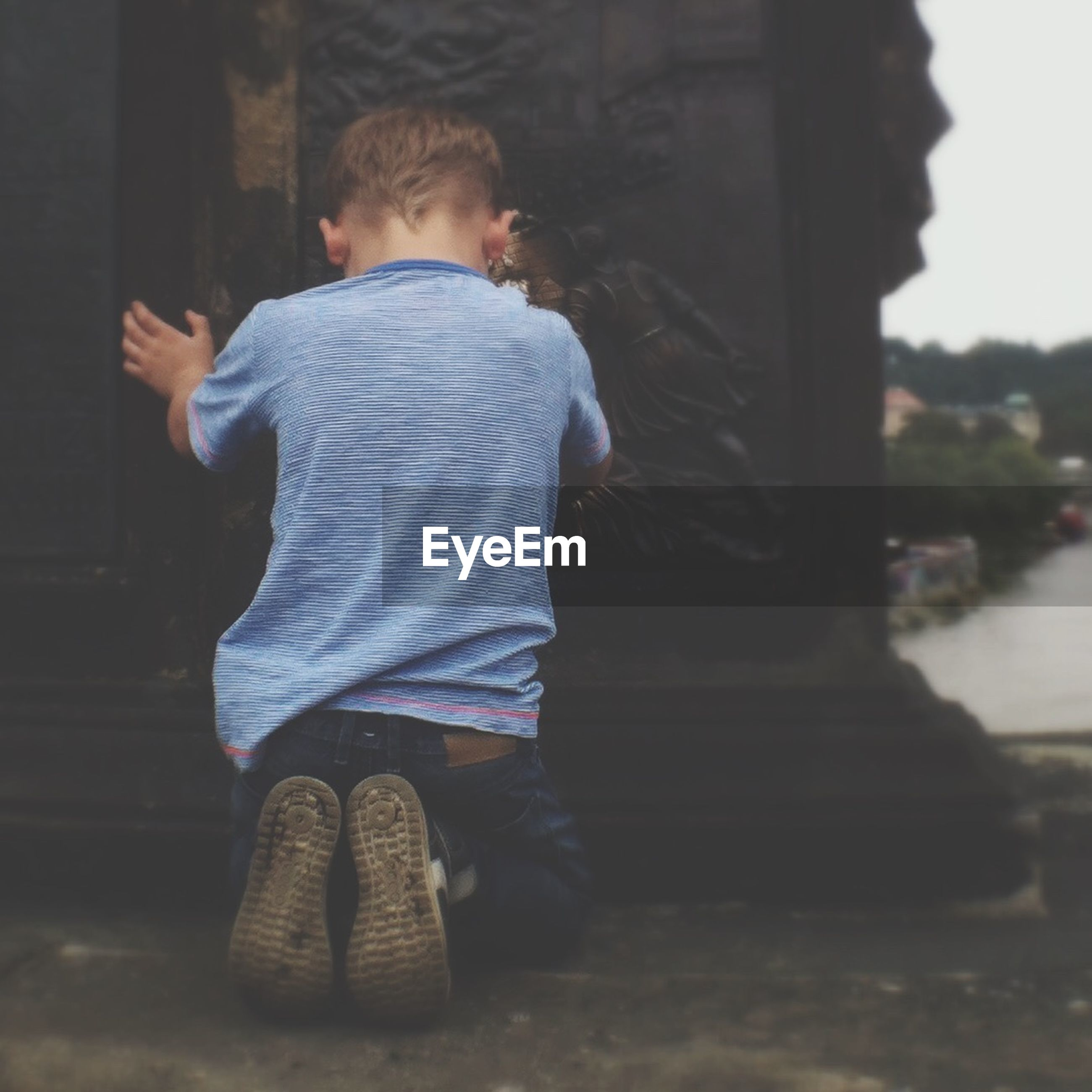 Rear view of boy kneeling in front of sculpture