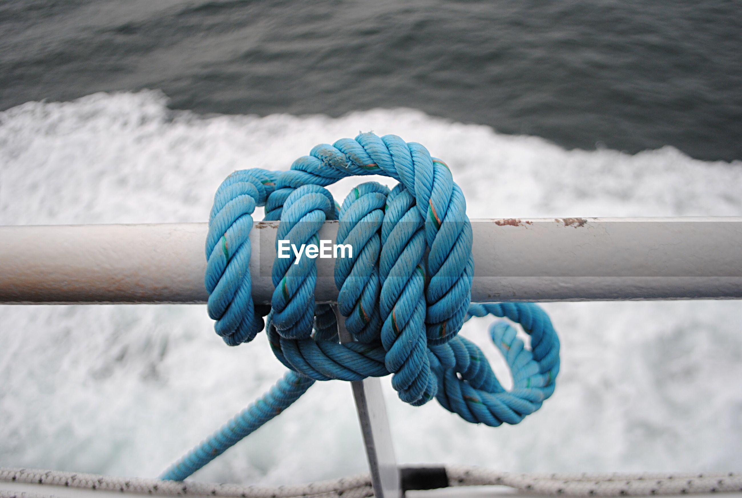 Close-up of rope tied to sailboat in sea