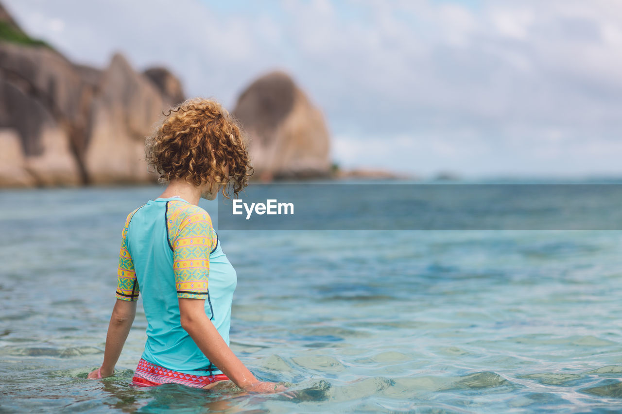 water, childhood, sea, child, one person, leisure activity, real people, rear view, lifestyles, beach, land, boys, day, nature, vacations, full length, casual clothing, trip, hair, hairstyle, outdoors, innocence, horizon over water