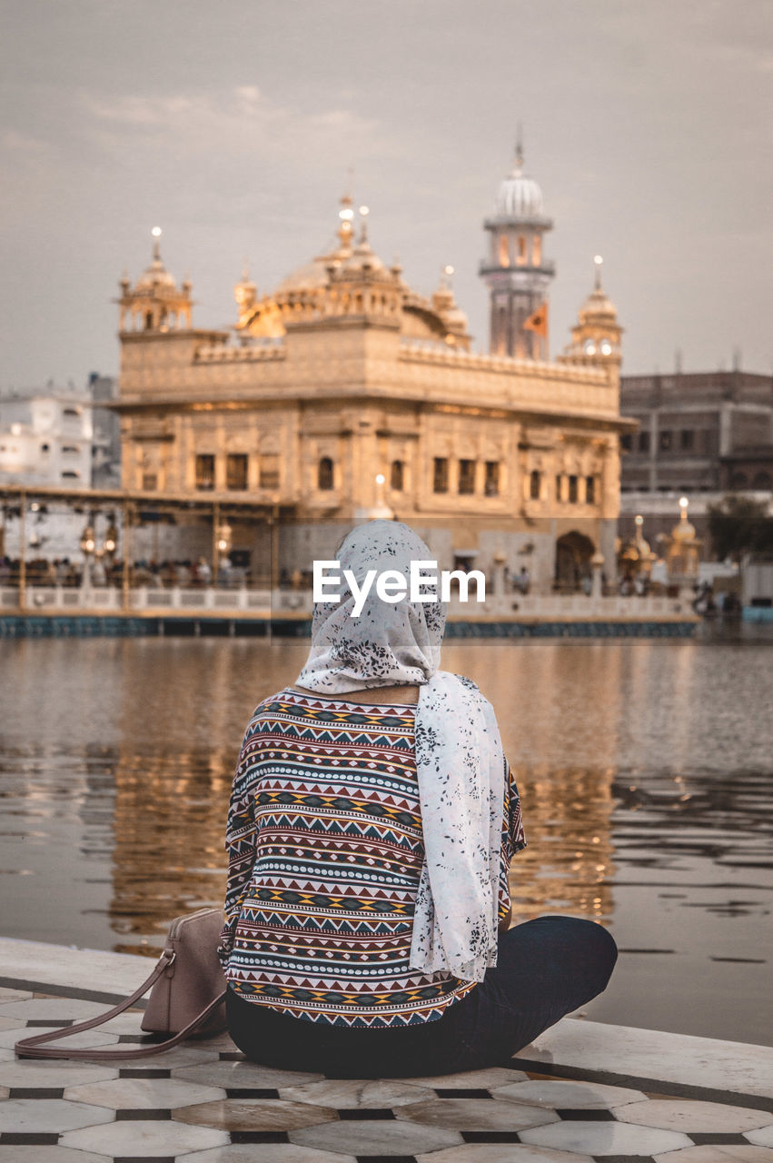 water, architecture, building exterior, built structure, rear view, one person, sitting, real people, sky, adult, nature, religion, day, spirituality, travel destinations, women, senior adult, waist up, outdoors, warm clothing, canal