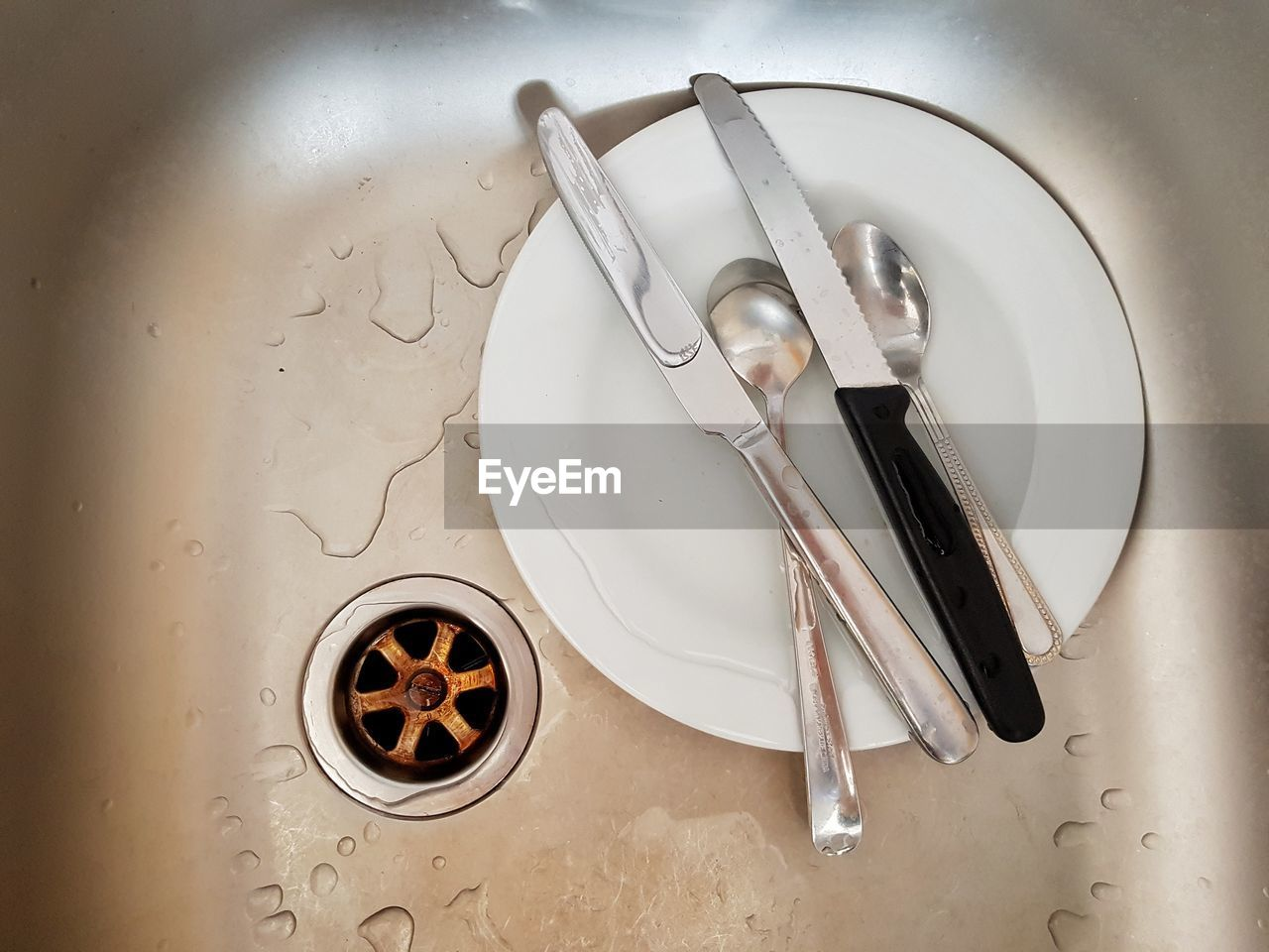 household equipment, eating utensil, kitchen utensil, indoors, fork, sink, knife, table knife, no people, high angle view, plate, metal, still life, directly above, drain, table, dirty, domestic room, dirt, water, crockery, silver colored