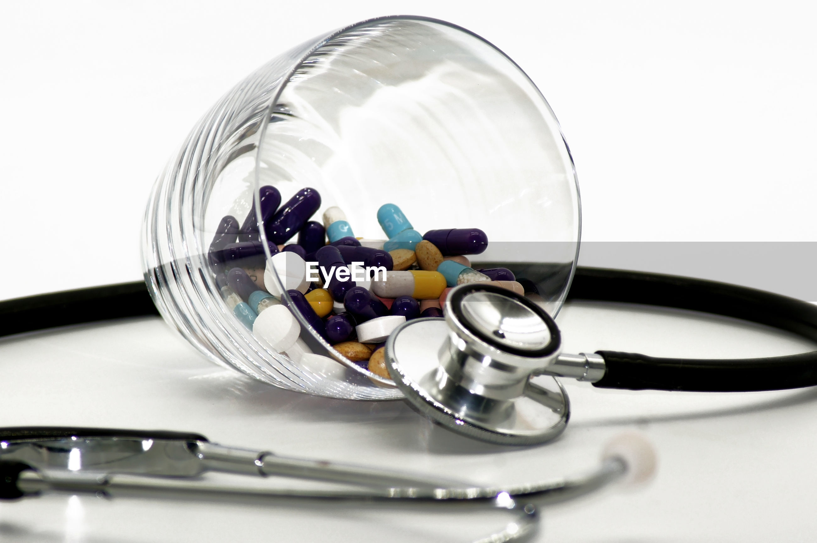 Close-up of pills and stethoscope against white background