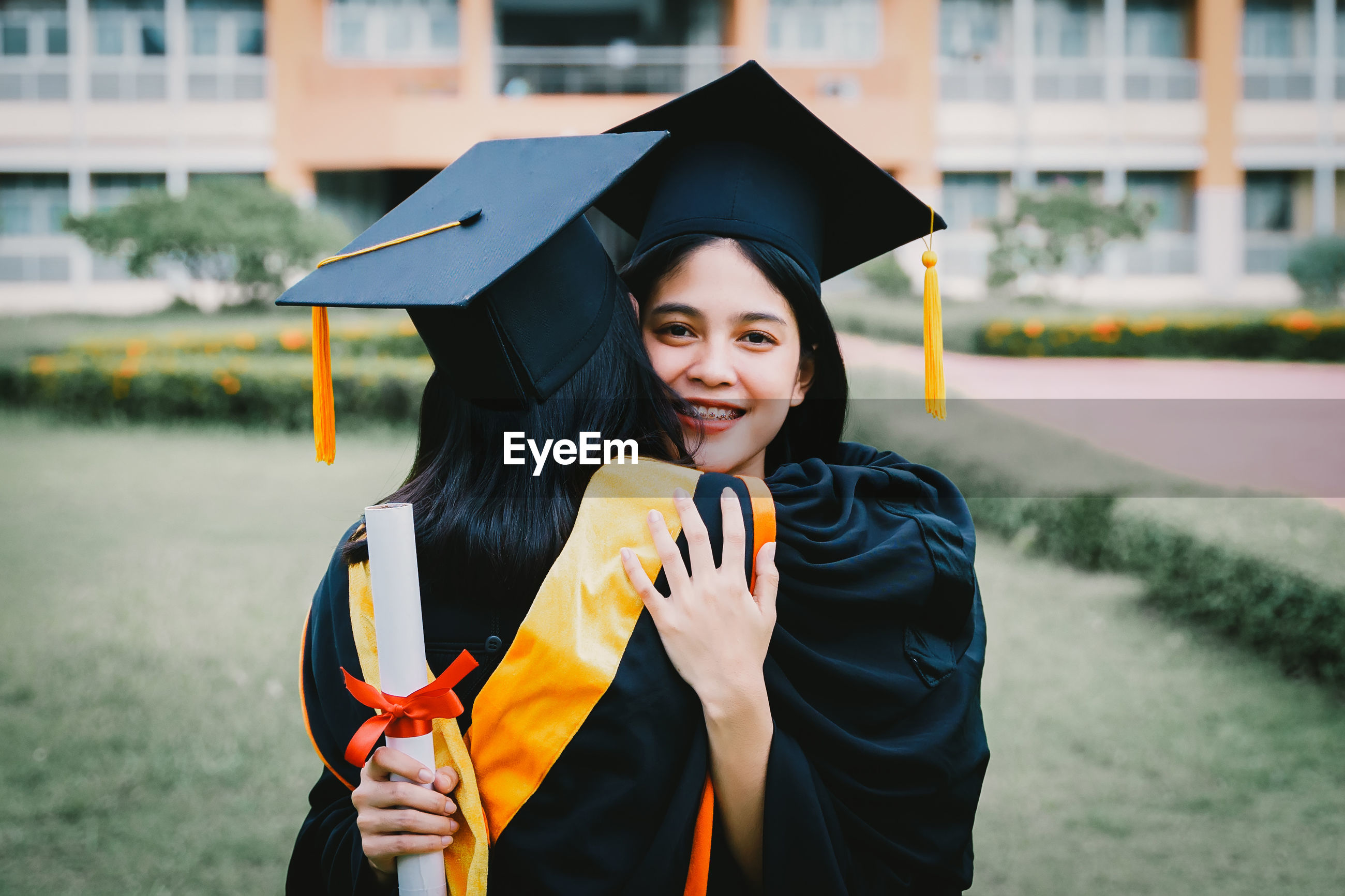 Portrait of young woman wearing graduation gown embracing friend at lawn