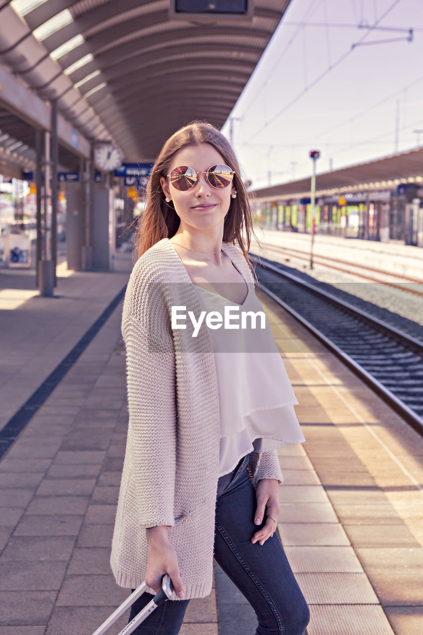 Portrait Of Young Woman With Luggage Waiting At Railroad Station Platform