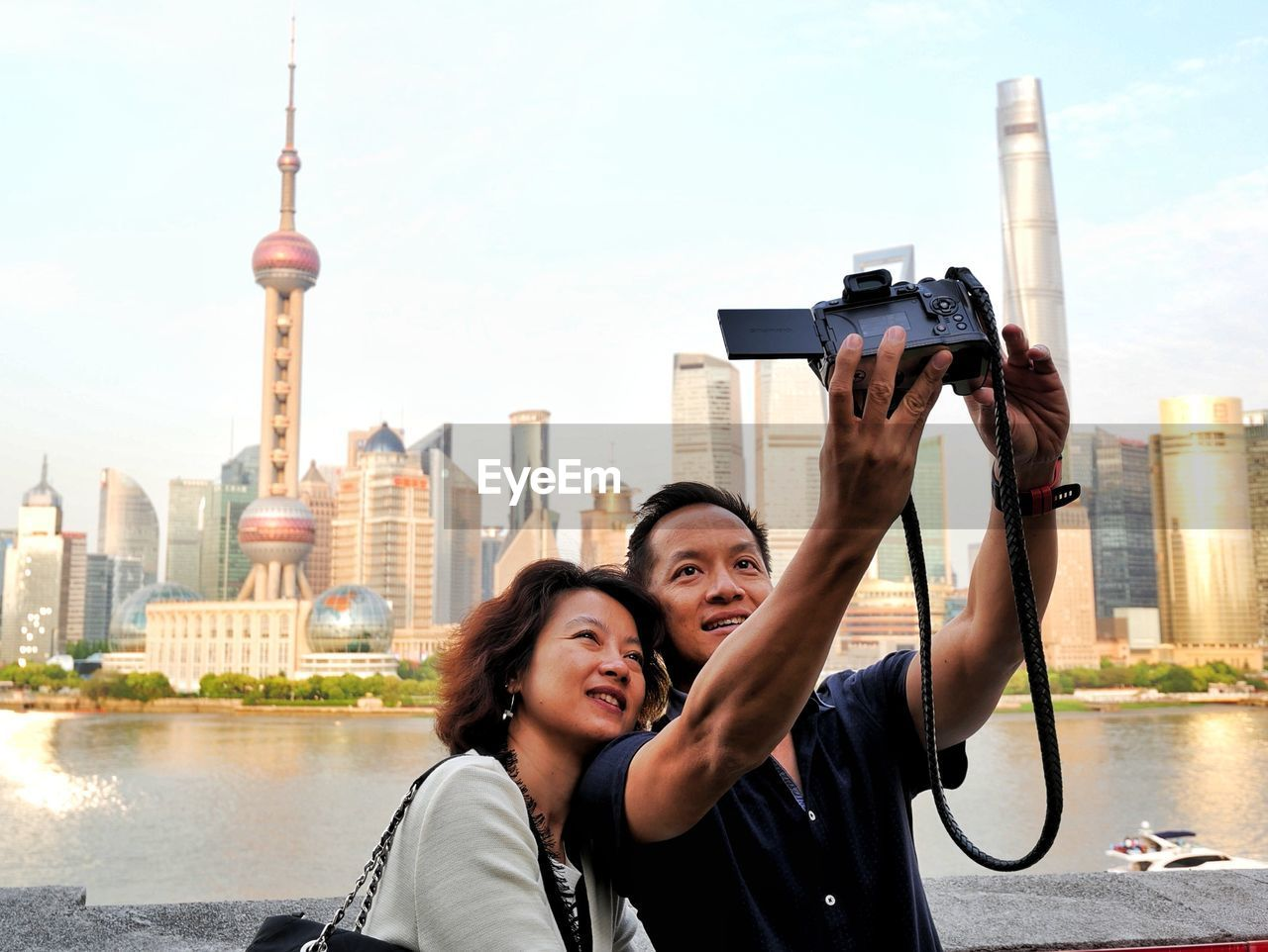 Mature couple taking selfie against skyscrapers