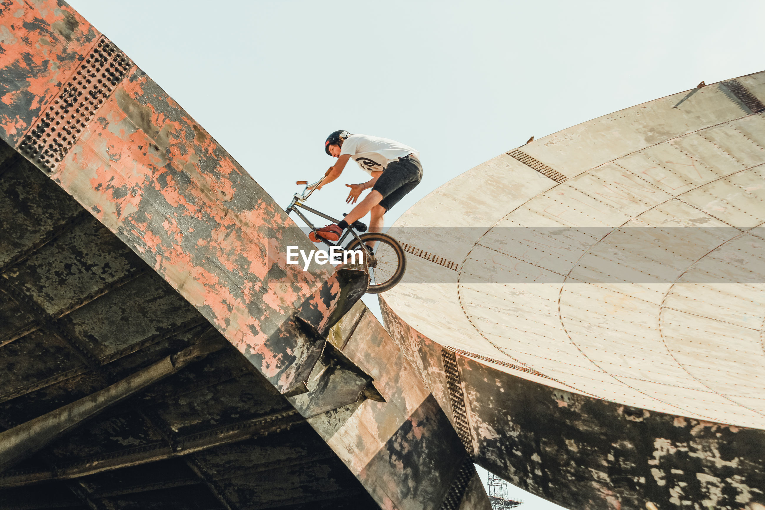 Low angle view of man riding bicycle on satellite dish