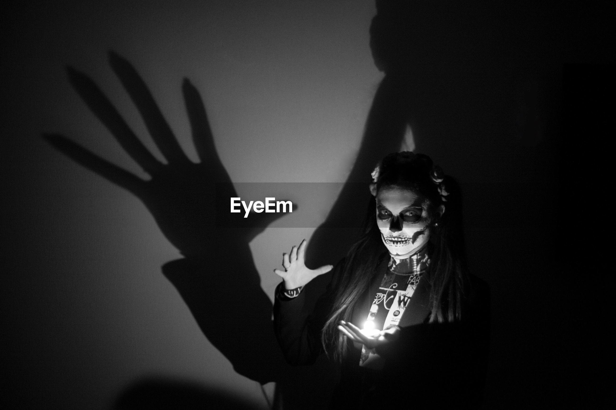 Portrait of spooky woman standing with illuminated lighting equipment in darkroom