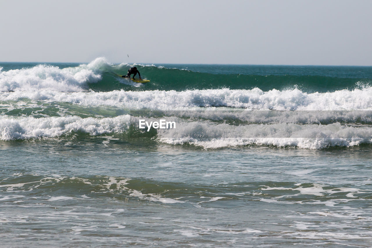 sea, water, motion, wave, sport, aquatic sport, horizon over water, adventure, waterfront, horizon, surfing, sky, beauty in nature, extreme sports, day, nature, people, leisure activity, skill, outdoors, power in nature
