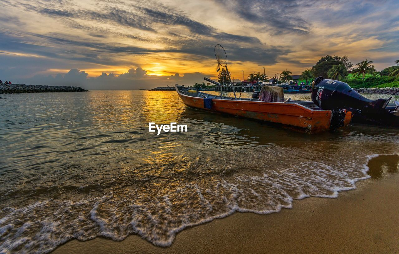 water, sunset, sky, nautical vessel, cloud - sky, sea, nature, beauty in nature, scenics, transportation, reflection, tranquility, mode of transport, moored, tranquil scene, waterfront, outdoors, beach, no people, day