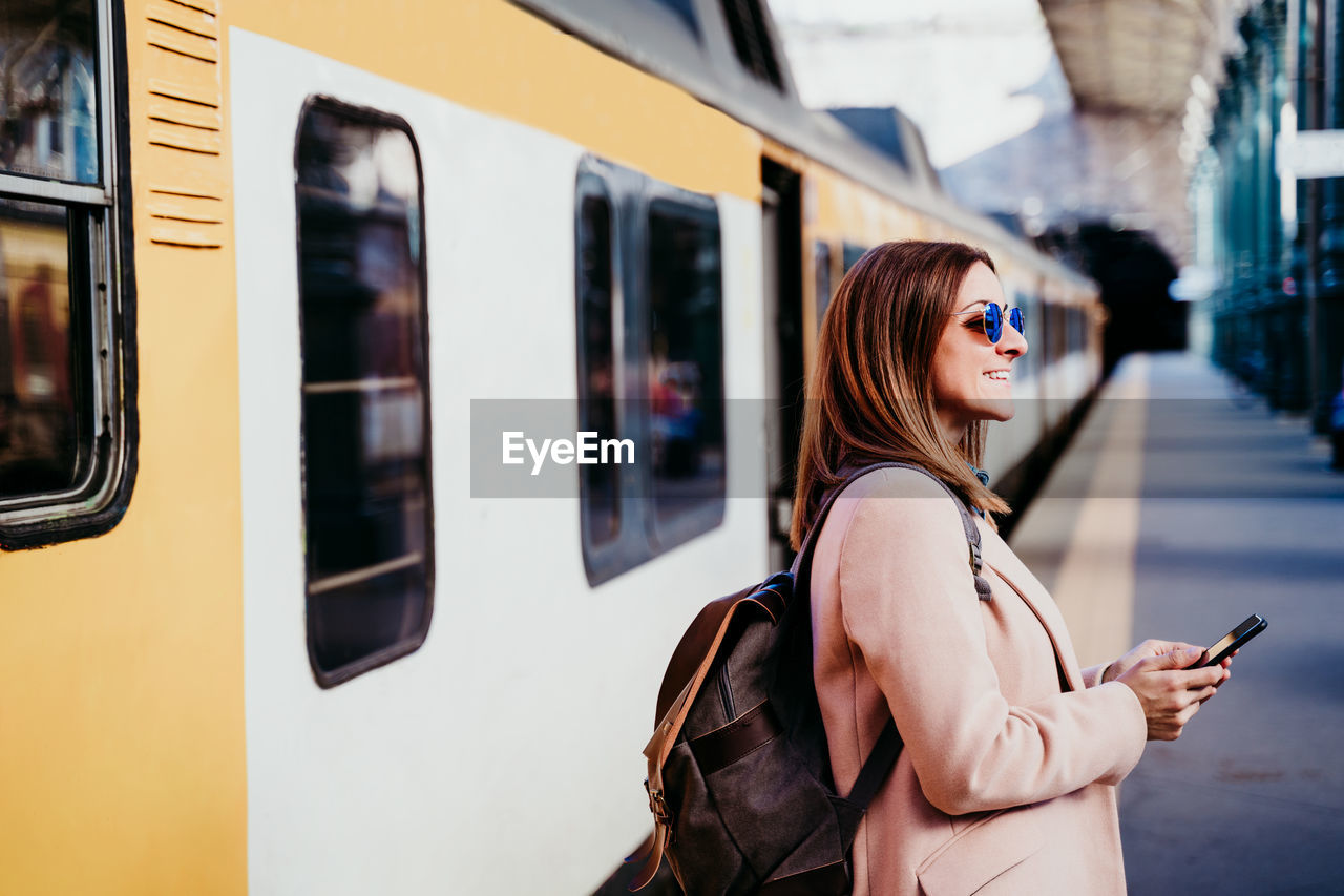 Full length of woman standing by train at railroad station