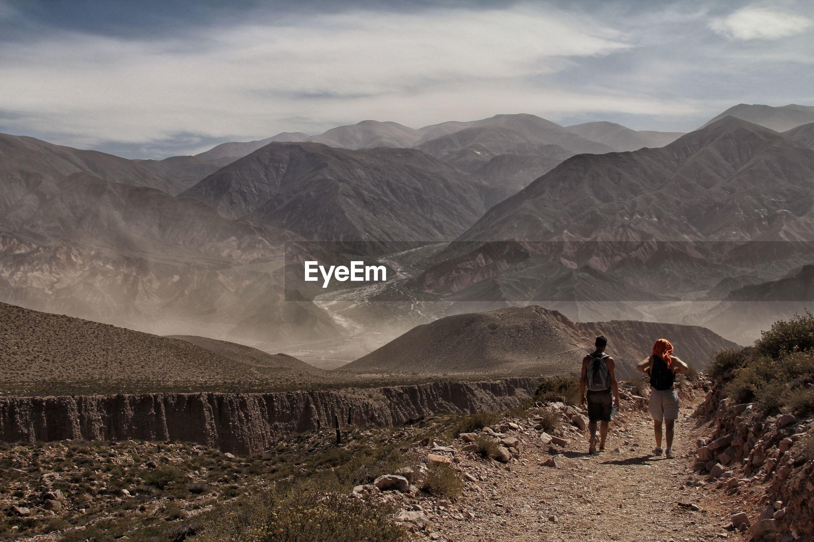 Two people walking on countryside landscape