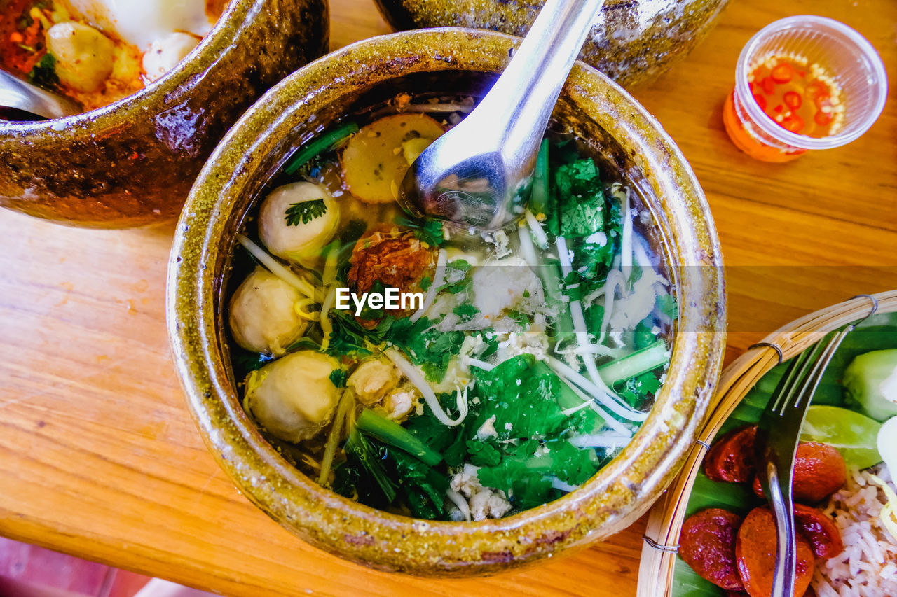 food and drink, bowl, food, healthy eating, ready-to-eat, freshness, soup, kitchen utensil, spoon, wellbeing, indoors, table, asian food, eating utensil, high angle view, vegetable, no people, directly above, still life, noodle soup, soup bowl, garnish, korean food, dinner, chinese food