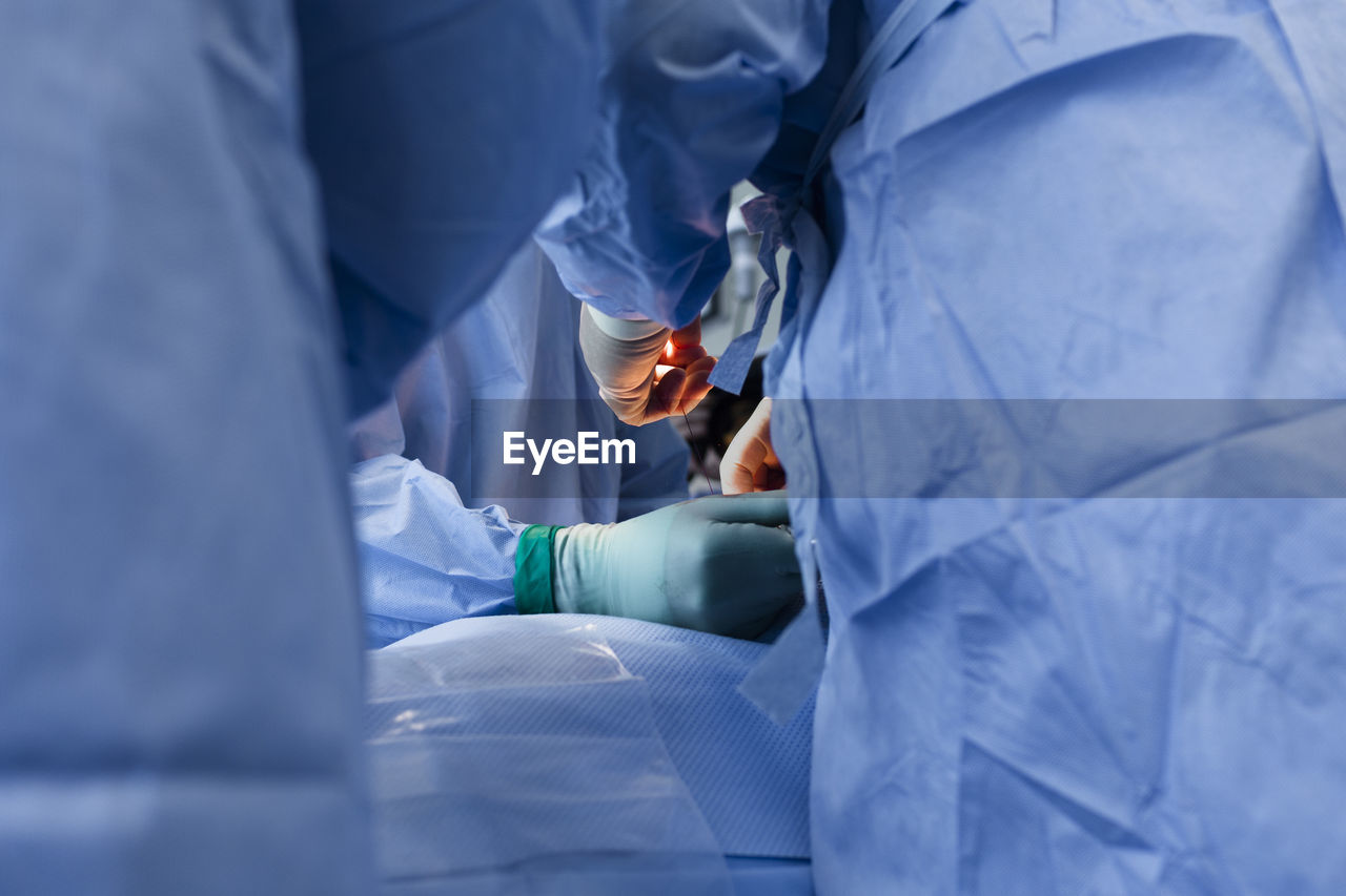 Midsection of surgeons operating