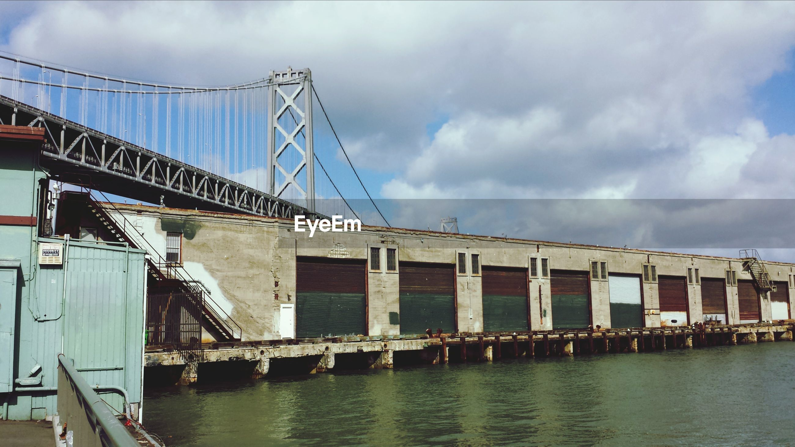 Commercial dock with bay bridge in background against cloudy sky