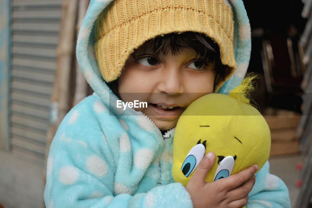 Close-Up Of Girl In Warm Clothing Holding Stuffed Toy Outdoors