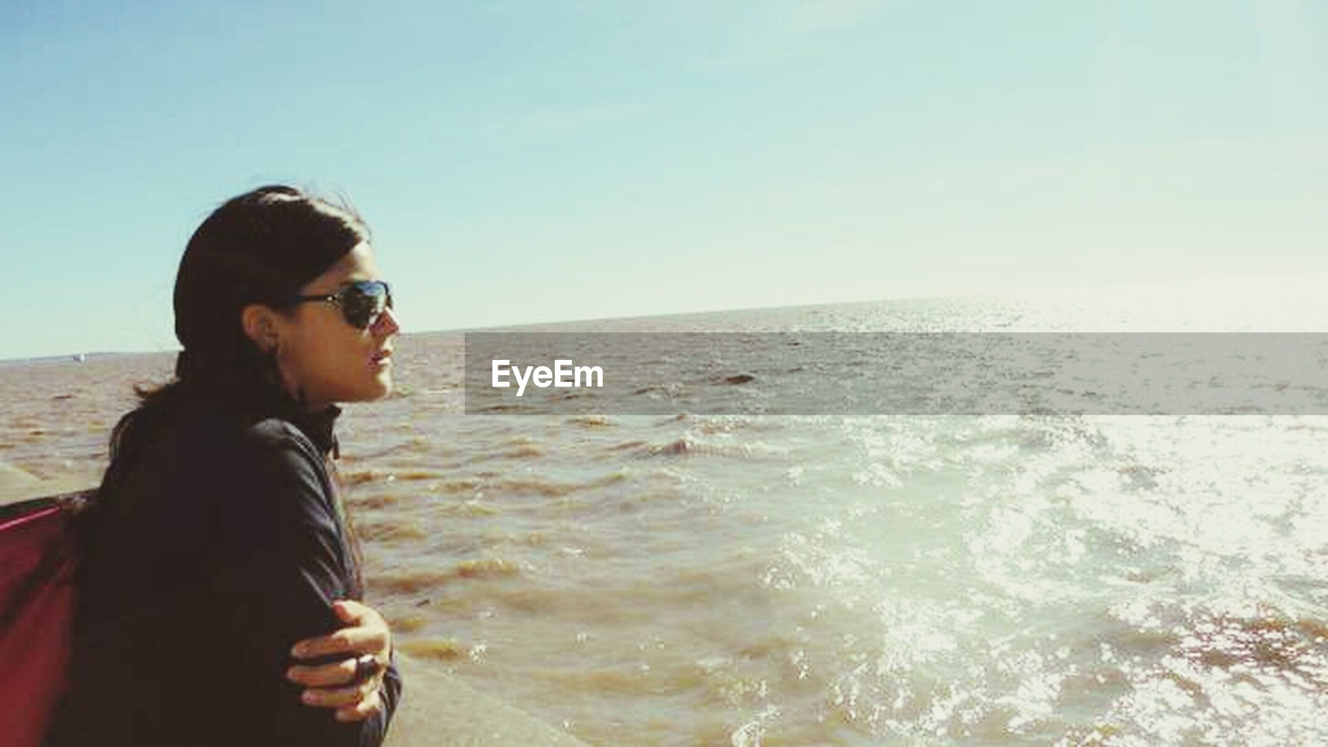 young adult, water, sea, lifestyles, person, leisure activity, beach, young women, portrait, looking at camera, horizon over water, sunglasses, clear sky, headshot, standing, sky, casual clothing