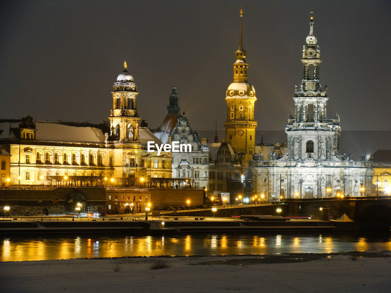 Illuminated church by river against sky at night