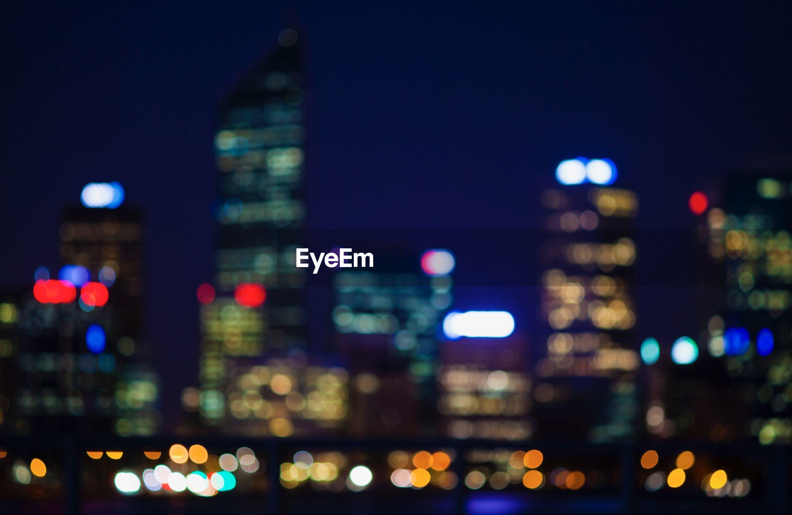DEFOCUSED IMAGE OF ILLUMINATED CITY BUILDINGS AT NIGHT